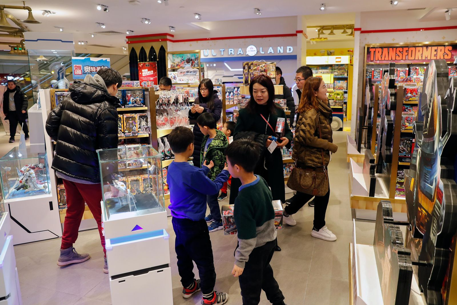 In this Saturday, Dec. 7, 2019, photo, Chinese parents and their children shop for toys at the American toy store FAO Schwarz at the capital city's popular shopping mall in Beijing. (AP Photo/Andy Wong)