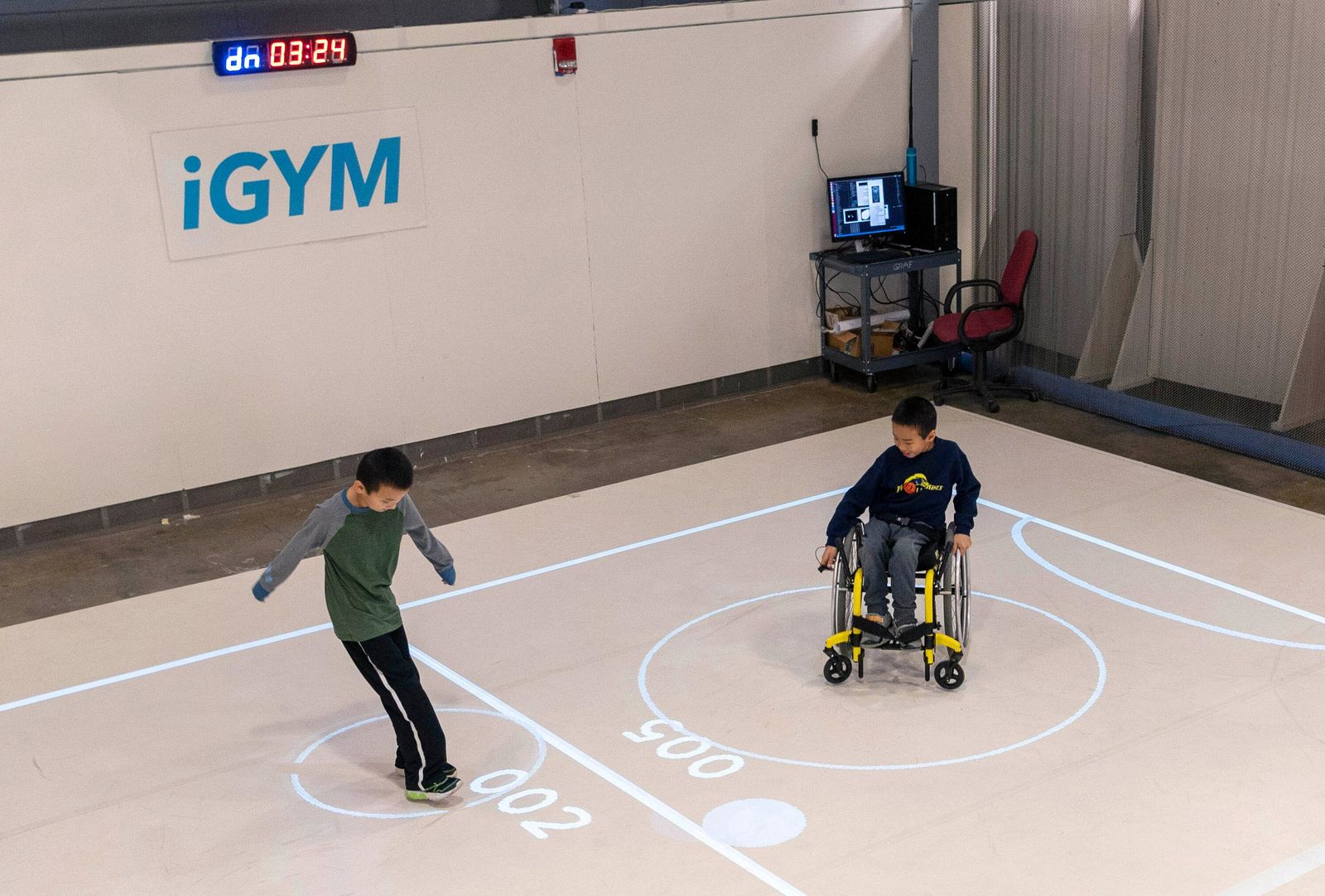 In this Nov. 17, 2019, photo provided by the University of Michigan, brothers Darren Kreps, left, and Bryan Kreps play a game modeled after soccer and air hockey using the iGYM system at the university in Ann Arbor, Mich. A University of Michigan research team has created iGYM, an augmented reality system that allows people with different levels of mobility to play and exercise together. (Roger Hart/University of Michigan via AP)