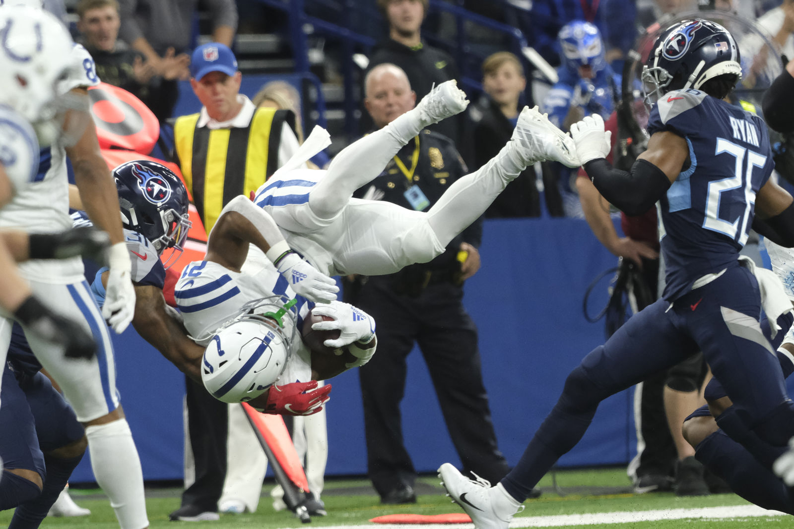 Indianapolis Colts running back Nyheim Hines (21) flips over between Tennessee Titans free safety Kevin Byard (31) and cornerback Logan Ryan (26) during the first half of an NFL football game in Indianapolis, Sunday, Dec. 1, 2019. (AP Photo/AJ Mast)