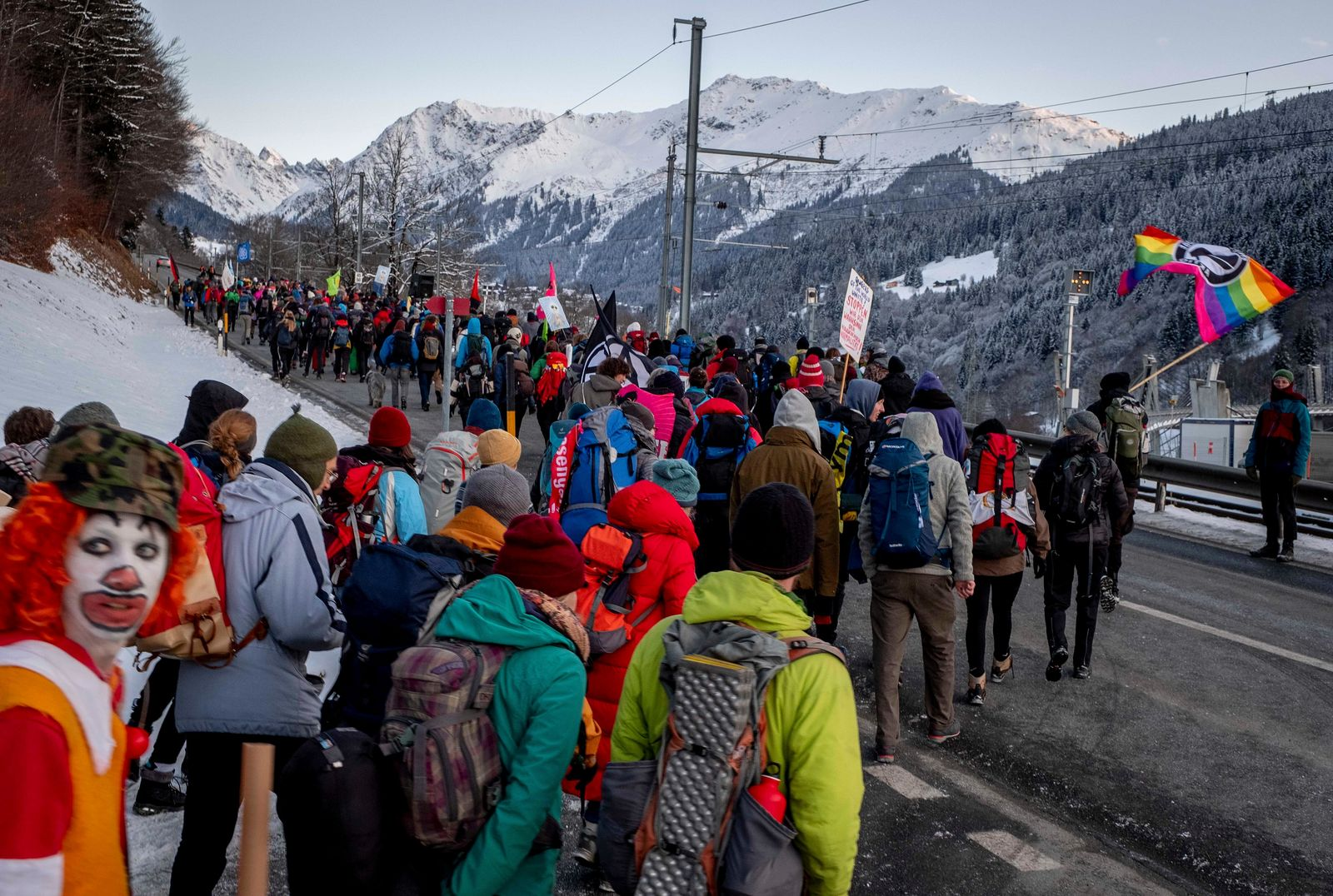 Hundreds of climate protesters who are on a three-day protest march from Landquart to Davos pass the city of Klosters, Switzerland, Monday, Jan. 20, 2020. The World Economic Forum will start on Tuesday. (AP Photo/Michael Probst)