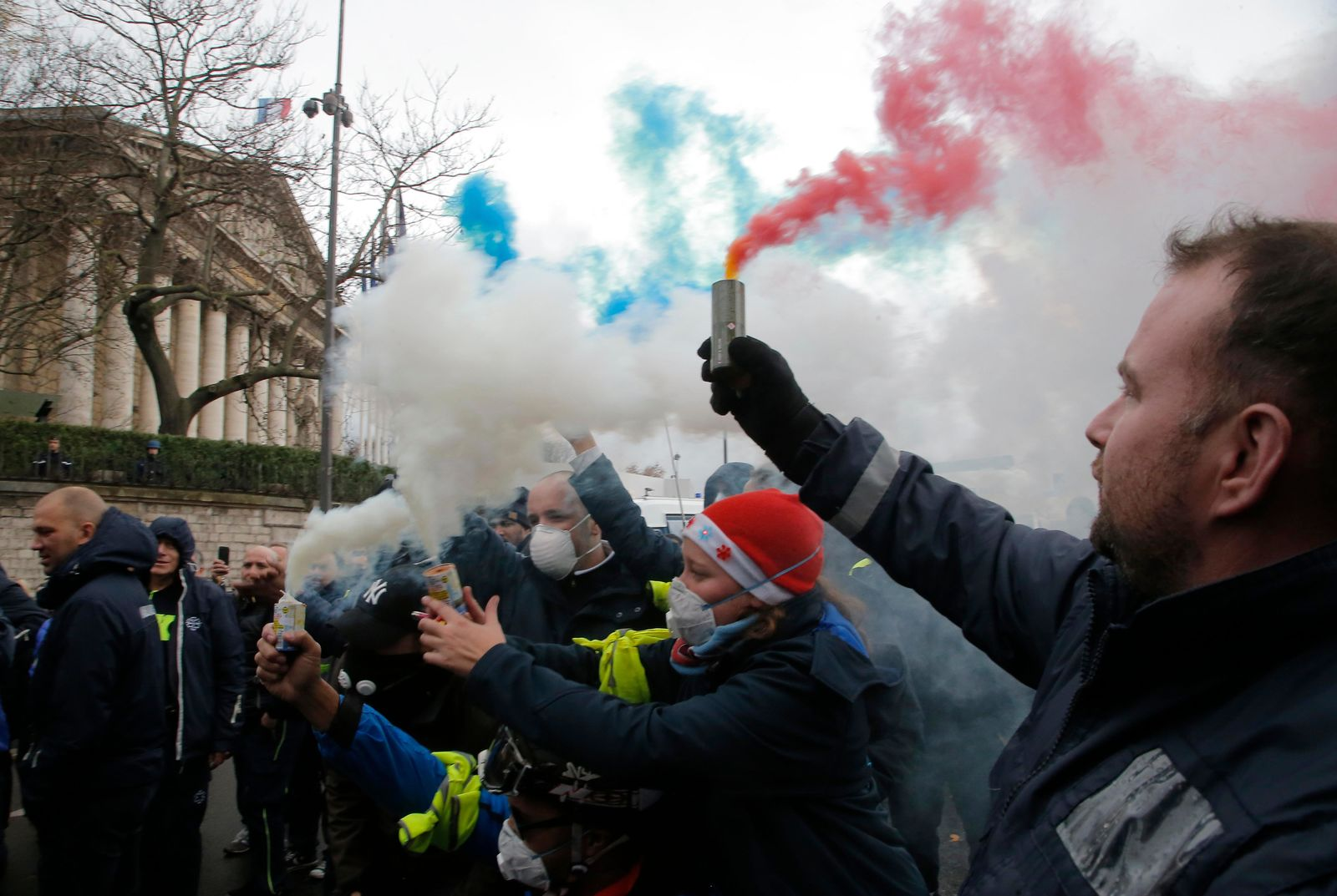 Ambulance workers hold flares outside the National Assembly in Paris, Monday, Dec. 3. (AP Photo/Michel Euler)