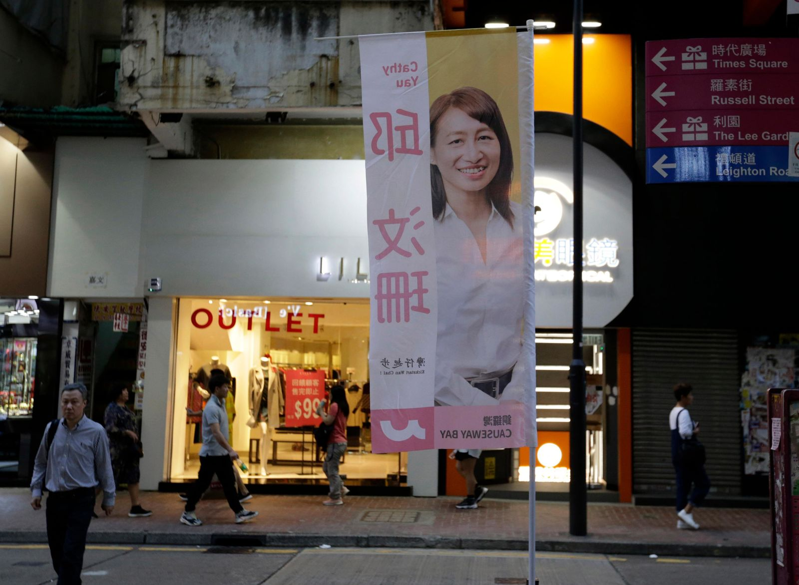 In this photo taken Thursday, Nov. 7, 2019, people walk past the campaign banner for district council candidate Cathy Yau at Causeway Bay in Hong Kong. AP Photo/Dita Alangkara)