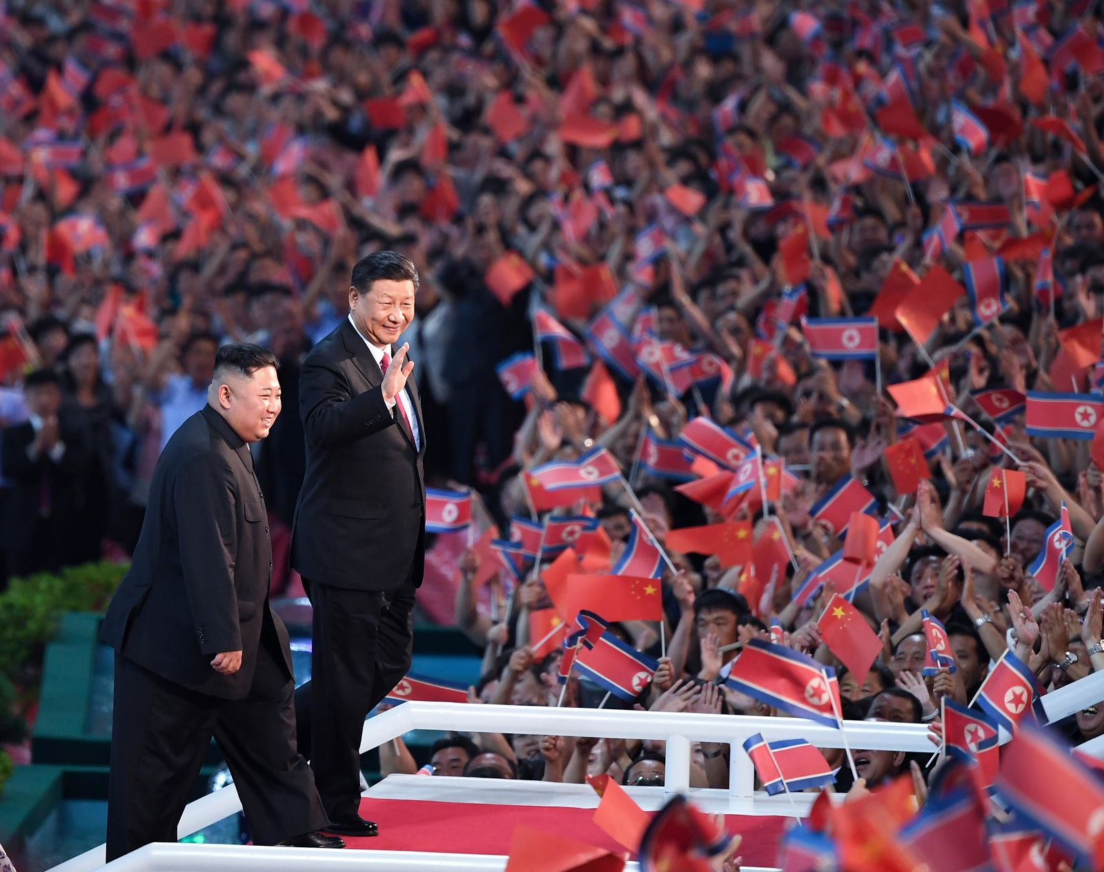 In this Thursday, June 20, 2019, photo released by China's Xinhua News Agency, spectators wave Chinese and North Korean flags as North Korean leader Kim Jong Un, left, and visiting Chinese President Xi Jinping attend a mass gymnastic performance at the May Day Stadium in Pyongyang, North Korea. North Korean leader Kim Jong Un, meeting in Pyongyang with Chinese President Xi Jinping, said Thursday that his country is waiting for a desired response in stalled nuclear talks with the United States. (Yan Yan/Xinhua via AP)