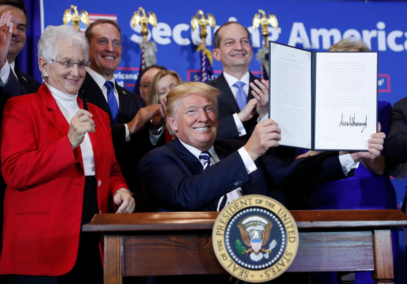 FILE - In this Aug. 31, 2018, file photo, President Donald Trump holds up a signed executive order on stage at the Harris Conference Center in Charlotte, N.C. The executive order is to make it easier for small businesses to group together to provide their workers with retirement plans. On the left is Rep. Virginia Foxx, R-N.C. Trump is now three for three. Each year of his presidency, he has issued more executive orders than did former President Barack Obama during the same time-span. (AP Photo/Pablo Martinez Monsivais, File)