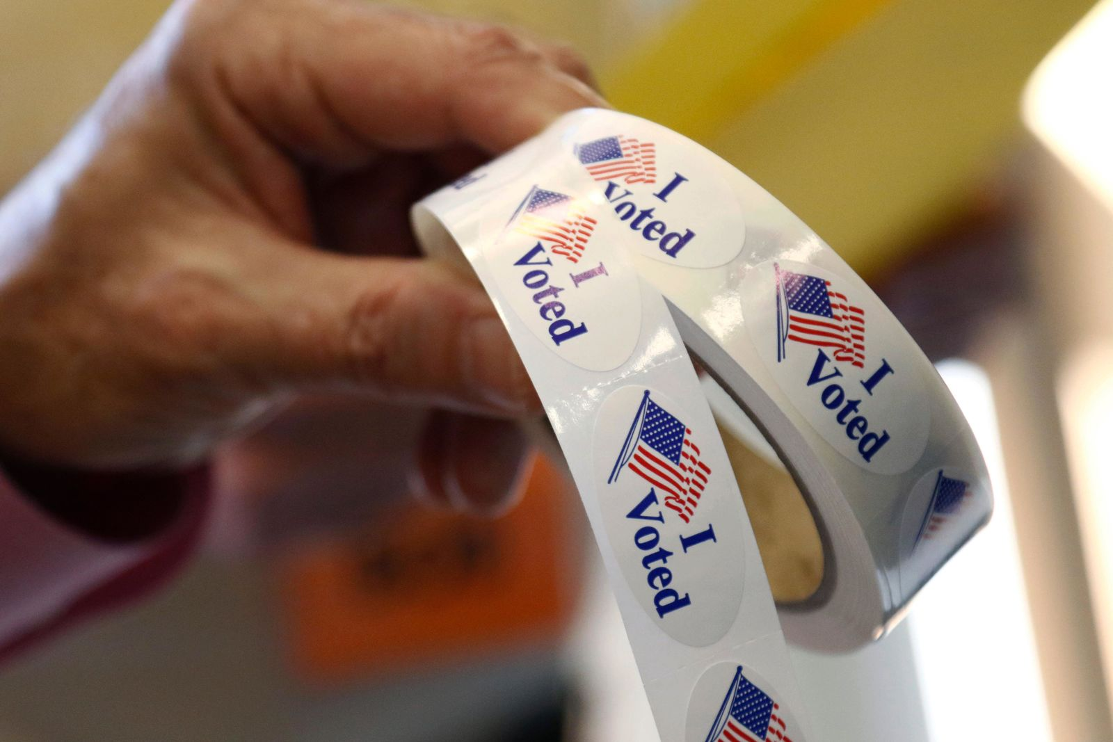 "Poll manager Larry Greer hands holds a roll of ""I Voted"" stickers given each person after voting in a runoff election Tuesday, Nov. 27, 2018 in Ridgeland, Miss.  Mississippi voters are deciding the last U.S. Senate race of the midterms, choosing between Espy and Republican Sen. Cindy Hyde-Smith.  (AP Photo/Rogelio V. Solis)"