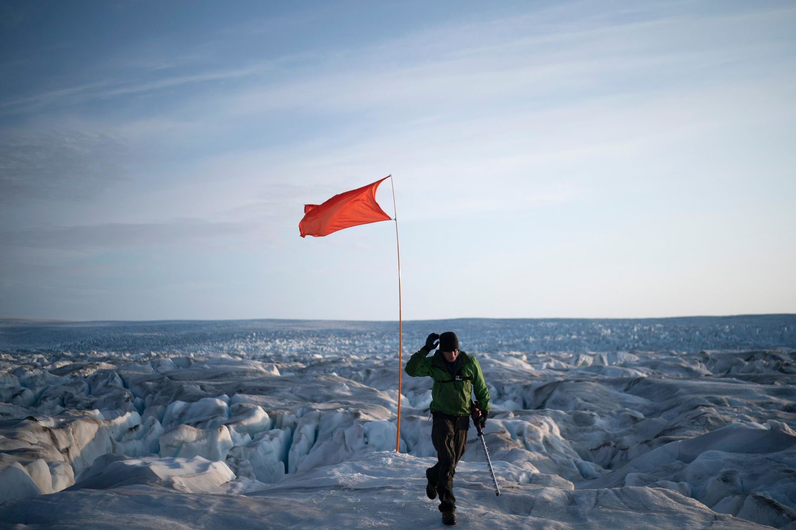 In this Aug. 16, 2019, photo, Brian Rougeux, NYU Field Safety Officer, walks after installing a flag to help identify a GPS position at the Helheim glacier, in Greenland.{ } (AP Photo/Felipe Dana)