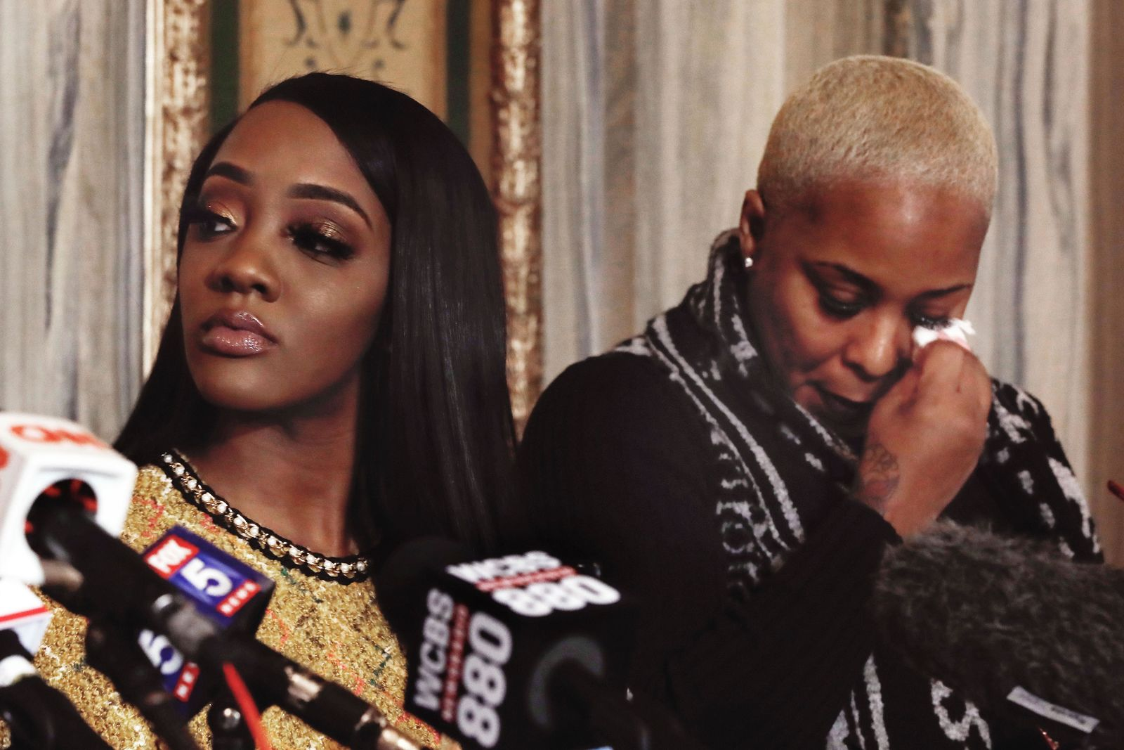"Faith Rodgers, left, listens during a news conference, as Michelle Kramer, mother of Dominique Gardner, wipes her eye after giving her statement about R&B singer R. Kelly in New York, Monday, Jan. 14, 2019. Kelly has been under fire since the recent airing of a Lifetime documentary ""Surviving R. Kelly ."" He has denied all allegations of sexual misconduct involving women and underage girls. (AP Photo/Richard Drew)"