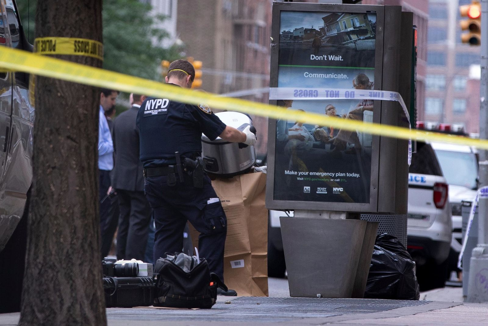 An investigator bags a suspicious package as evidence after it was thought to be an explosive device in Manhattan's Chelsea neighborhood Friday, Aug. 16, 2019, in New York. (AP Photo/Kevin Hagen).