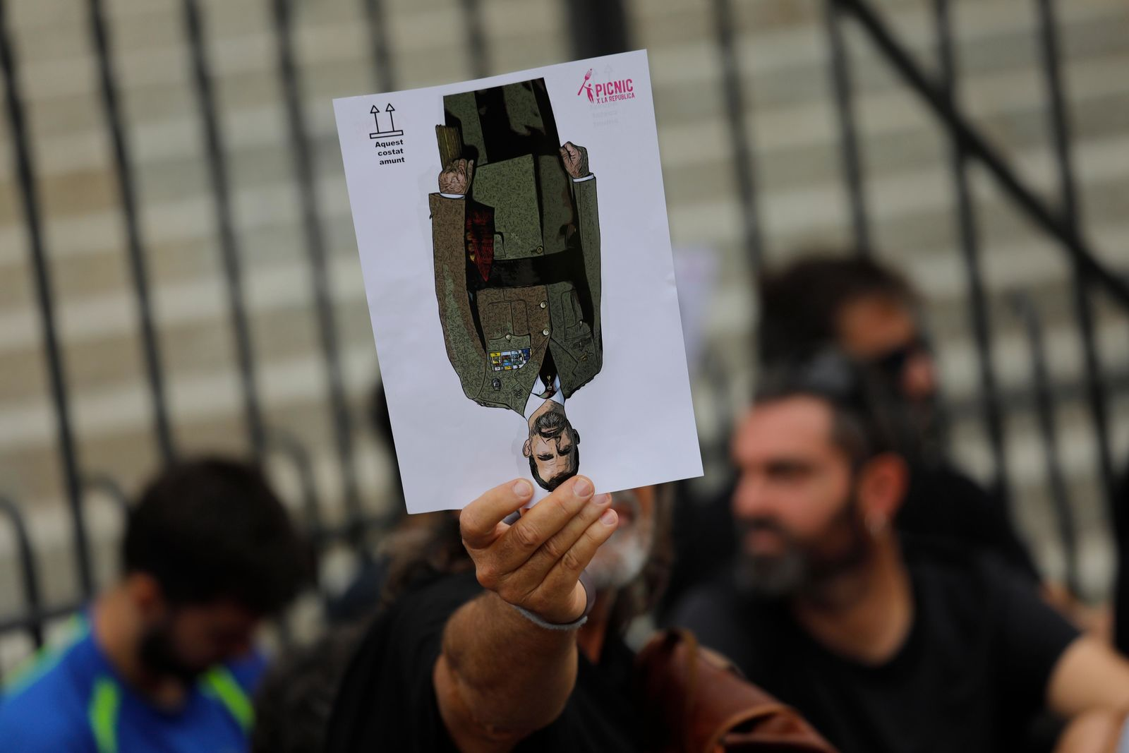 A protester holds a portrait of Spain's King Felipe upside down during a pro-independence gathering on the fifth day of protests over the conviction of a dozen Catalan independence leaders in Barcelona, Spain, Friday, Oct. 18, 2019. (AP Photo/Bernat Armangue)