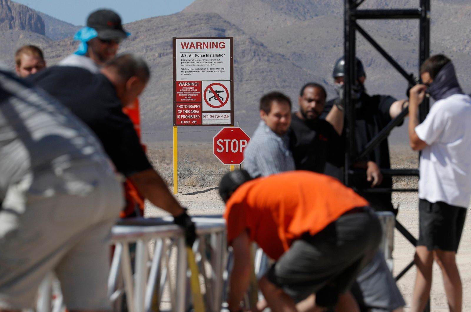 "Workers erect a stage near a replica Area 51 gate sign at the Alien Research Center, Wednesday, Sept. 18, 2019, in Hiko, Nev. Visitors descending on the remote Nevada desert for ""Storm Area 51"" are from Earth, not outer space. No one knows what to expect, but the two tiny towns of Rachel and Hiko near the once-secret military research site are preparing for an influx of people over the next few days. (AP Photo/John Locher)"