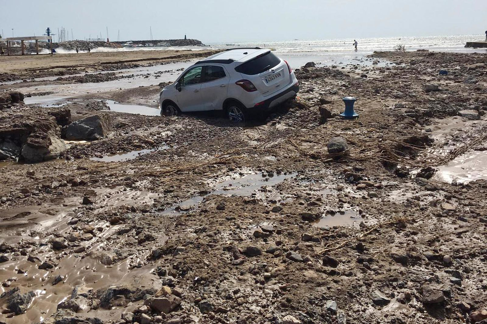 A car lies in the mud after a flood in San Jose, Almeria in south-eastern Spain, Friday Sept. 13, 2019. Spanish authorities say that heavy storms in the southeast have claimed another victim, bringing the death toll from the extremely bad weather to three. (AP Photo/Serge Carthwright)