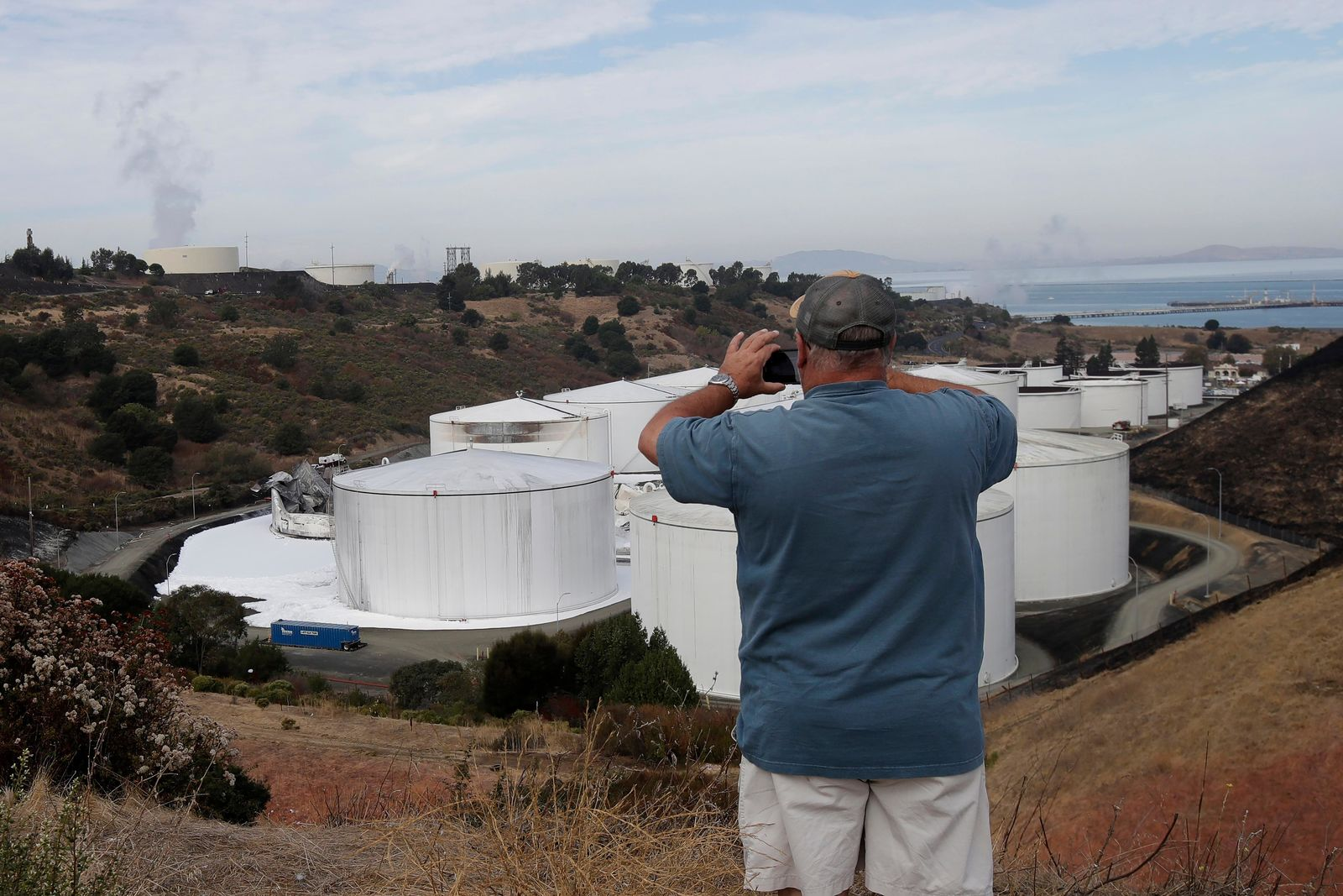 Mark Storey takes photos of damage from a Tuesday, Oct. 15, 2019, fire at NuStar Energy fuel storage facility in Crockett, Calif., Wednesday, Oct. 16, 2019. Officials were trying to determine Wednesday if a 4.5 magnitude earthquake triggered an explosion at a fuel storage facility in the San Francisco Bay Area that started a fire and trapped thousands in their homes for hours because of potentially unhealthy air. (AP Photo/Jeff Chiu)