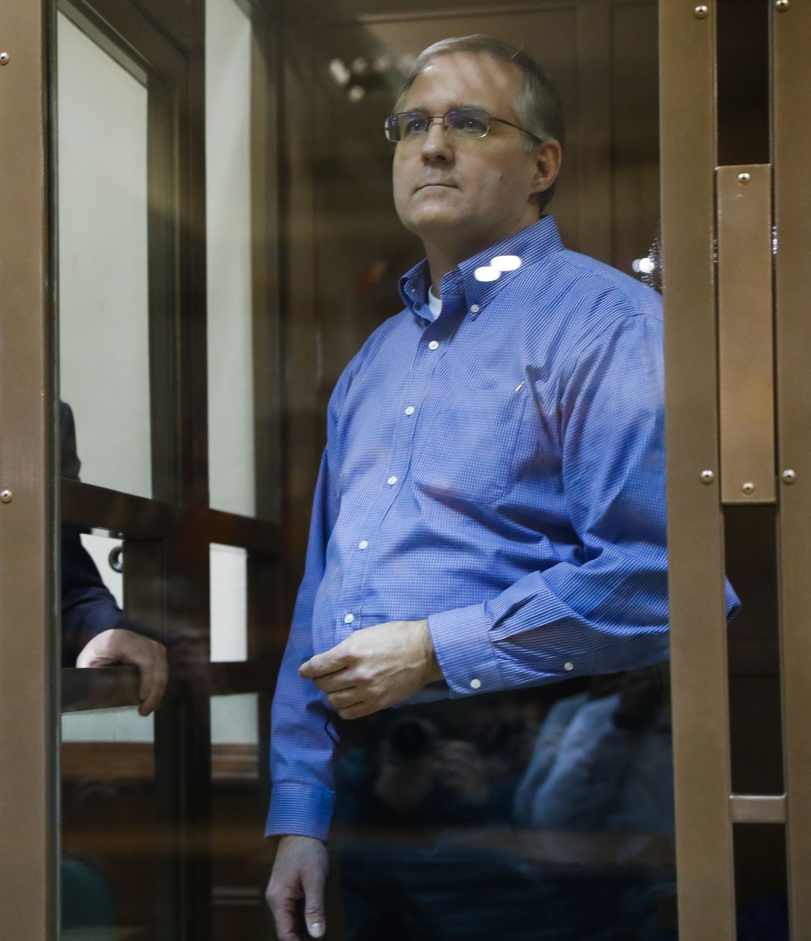Paul Whelan, a former U.S. Marine, who was arrested in Moscow at the end of last year looks through a cage's glass in a court room in Moscow, Russia, Tuesday, Jan. 22, 2019. (AP Photo/Pavel Golovkin)