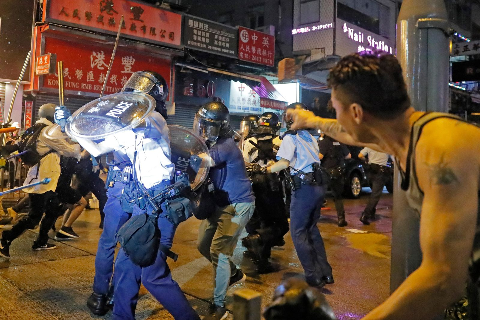 A man throws a brick to policemen on a street during a protest in Hong Kong, Sunday, Aug. 25, 2019. (AP Photo/Kin Cheung)
