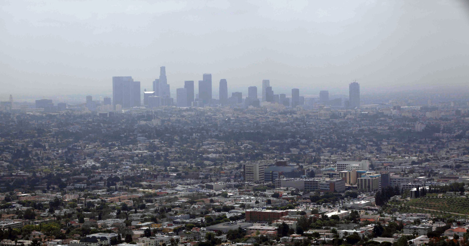 FILE - In this April 28, 2009 file photo smog covers downtown Los Angeles. A new study released Monday, March 11, 2019, says African-Americans and Hispanics breathe in far more deadly air pollution than they are responsible for making. (AP Photo/Nick Ut, File)