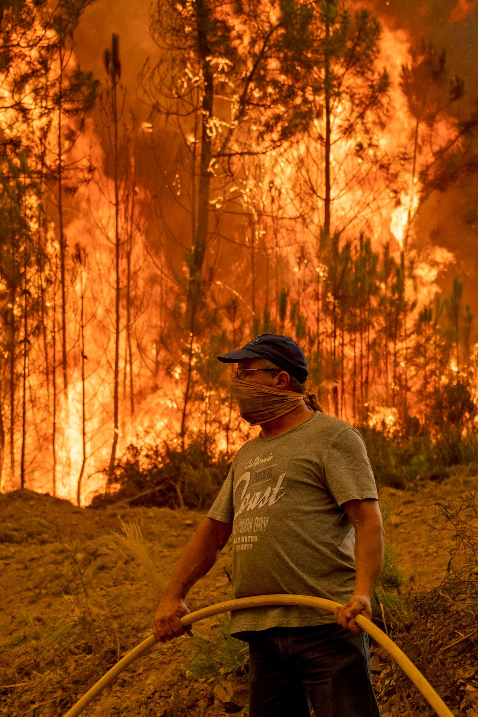 A villager tries to extinguish a wildfire at the village of Chaveira, near Macao, in central Portugal on Monday, July 22, 2019. (AP Photo/Sergio Azenha)