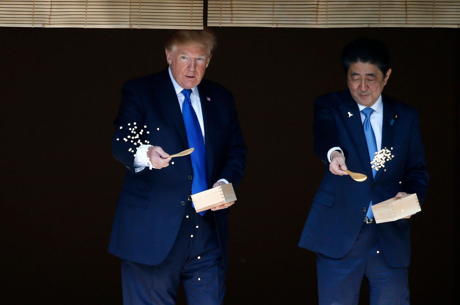 FILE - In this Nov. 6, 2017, file photo, U.S. President Donald Trump, left, and Japanese Prime Minister Shinzo Abe feed carp before their working lunch at Akasaka Palace in Tokyo. (Toru Hanai/Pool Photo via AP, File)