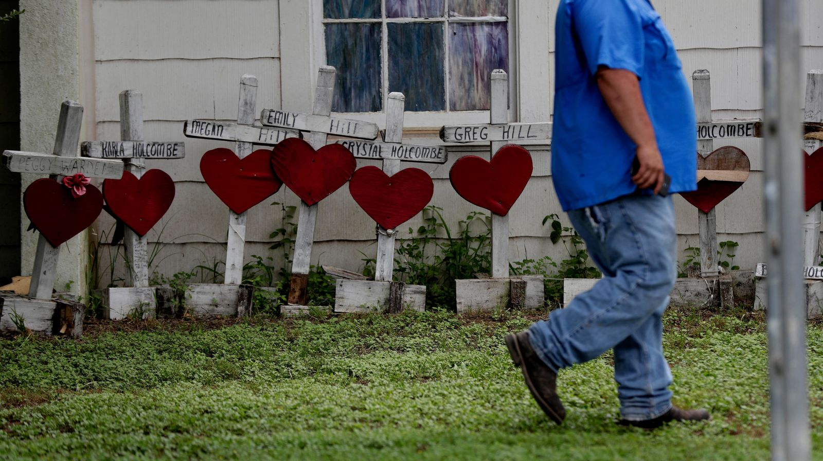 A man passes old memorial crosses on the side of a church building following a dedication ceremony for a new sanctuary and memorial room at the First Baptist Church in Sutherland Springs, Texas, Sunday, May 19, 2019. In 2017 a gunman opened fire at the church and killed more than two dozen congregants. (AP Photo/Eric Gay)