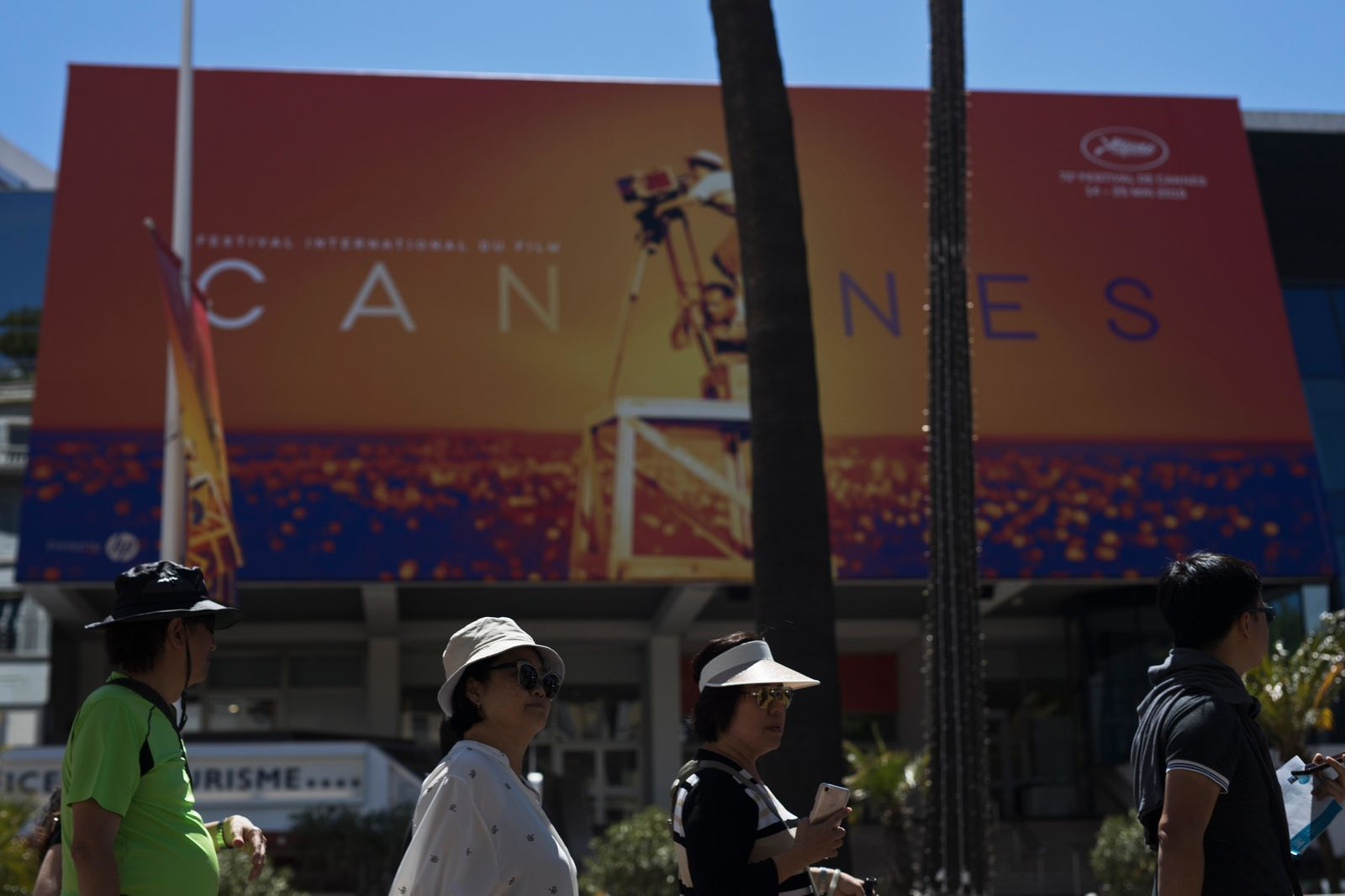 Festival goers walk by the Palais des festivals during the 72nd international film festival, Cannes, southern France, Monday, May 13, 2019. The Cannes film festival runs from May 14th until May 25th 2019. (AP Photo/Petros Giannakouris)