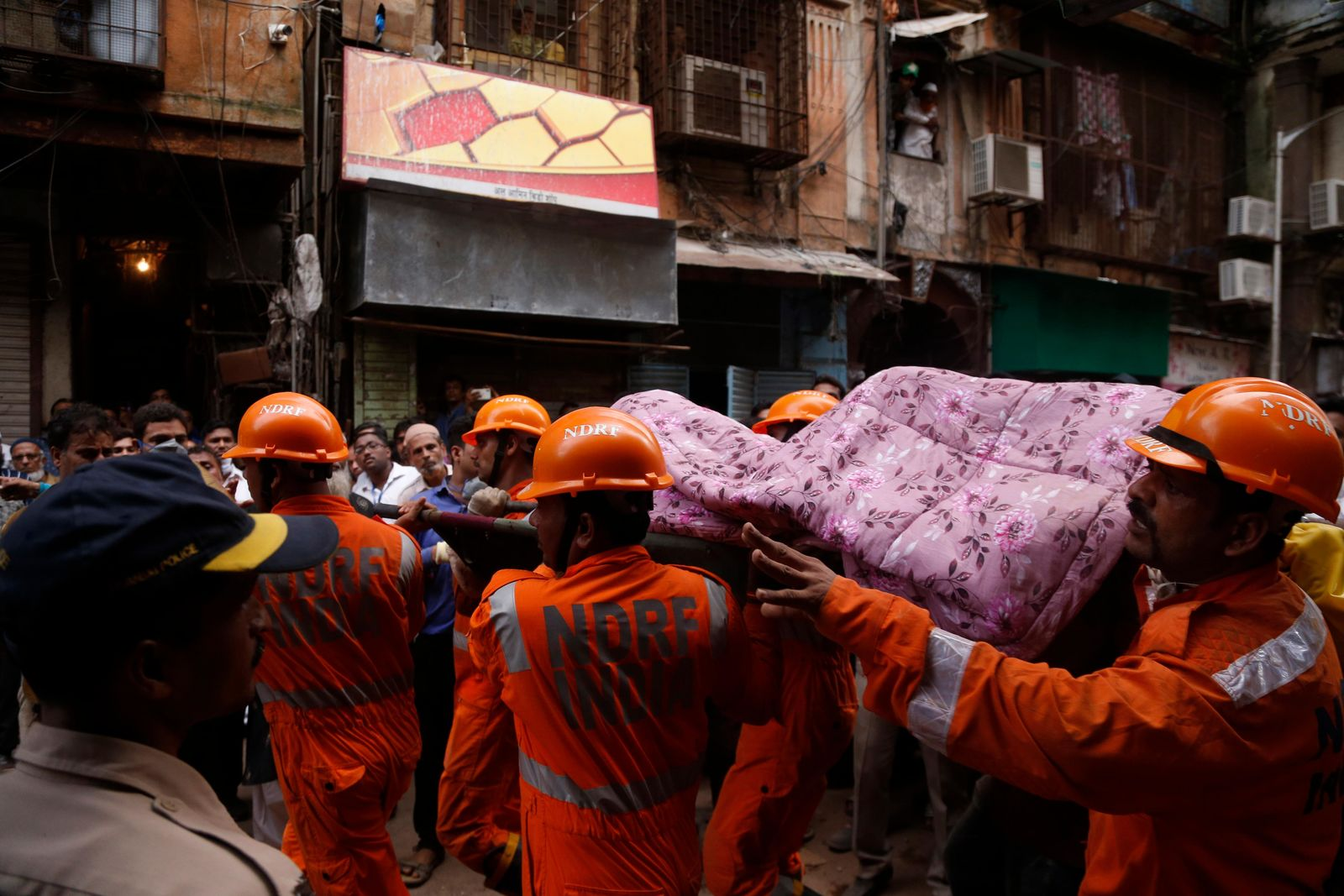 Rescuers carry the body of a victim at the site of a building that collapsed in Mumbai, India, Tuesday, July 16, 2019.{ } (AP Photo/Rafiq Maqbool)