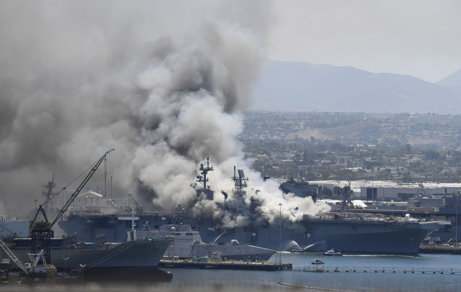 Smoke rises from the USS Bonhomme Richard at Naval Base San Diego Sunday, July 12, 2020, in San Diego after an explosion and fire Sunday on board the ship at Naval Base San Diego. (AP Photo/Denis Poroy)