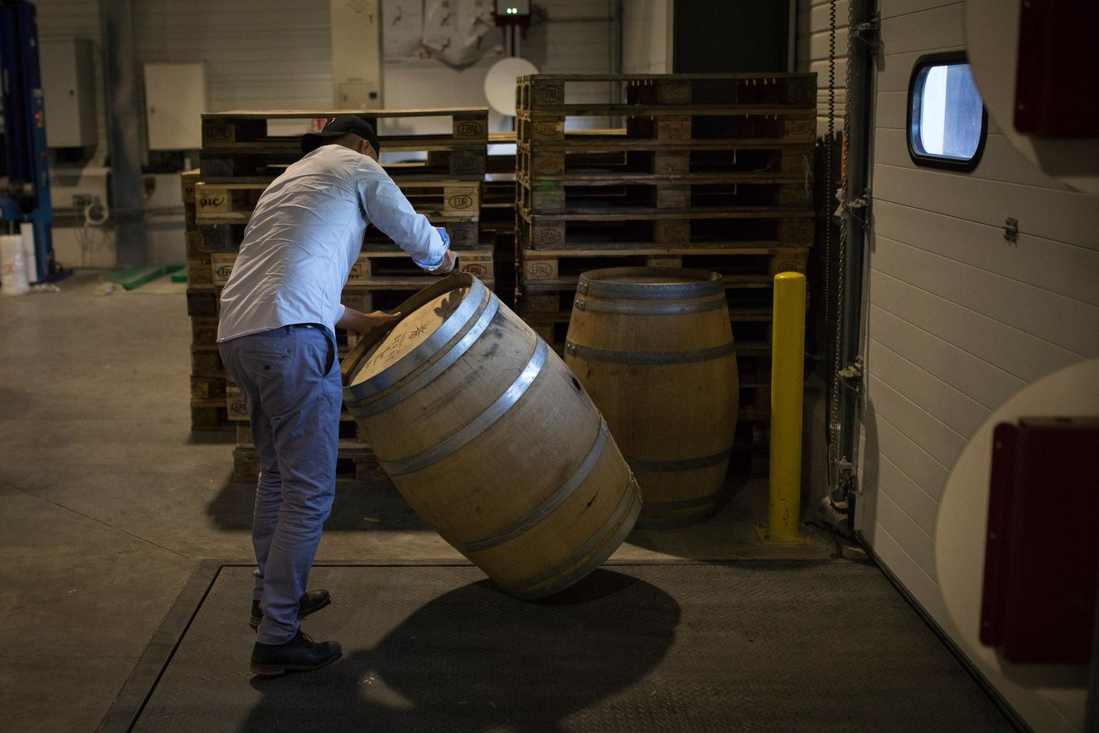 An employee moves an empty barrel in the shipping warehouse of the French wine producer MDCV, in the Chateau des Bertrands in Le Cannet-des-Maures, in the Provence region, Thursday Oct. 10, 2019. (AP Photo/Daniel Cole)