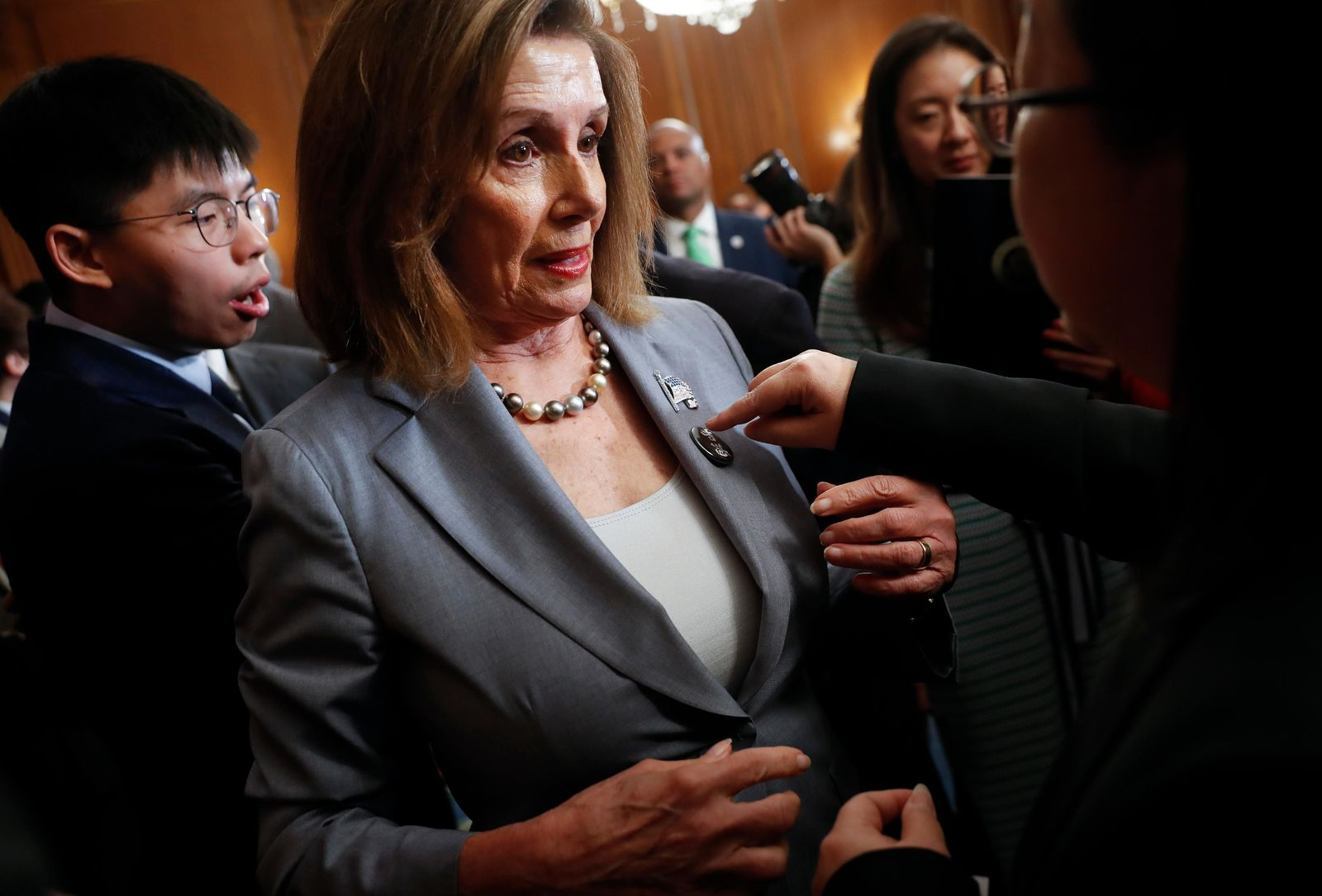 House Speaker Nancy Pelosi is given a lapel pin by a Hong Kong activist following a news conference on human rights in Hong Kong on Capitol Hill in Washington, Wednesday, Sept. 18, 2019. Behind Pelosi is Hong Kong activist Joshua Wong. (AP Photo/Pablo Martinez Monsivais)