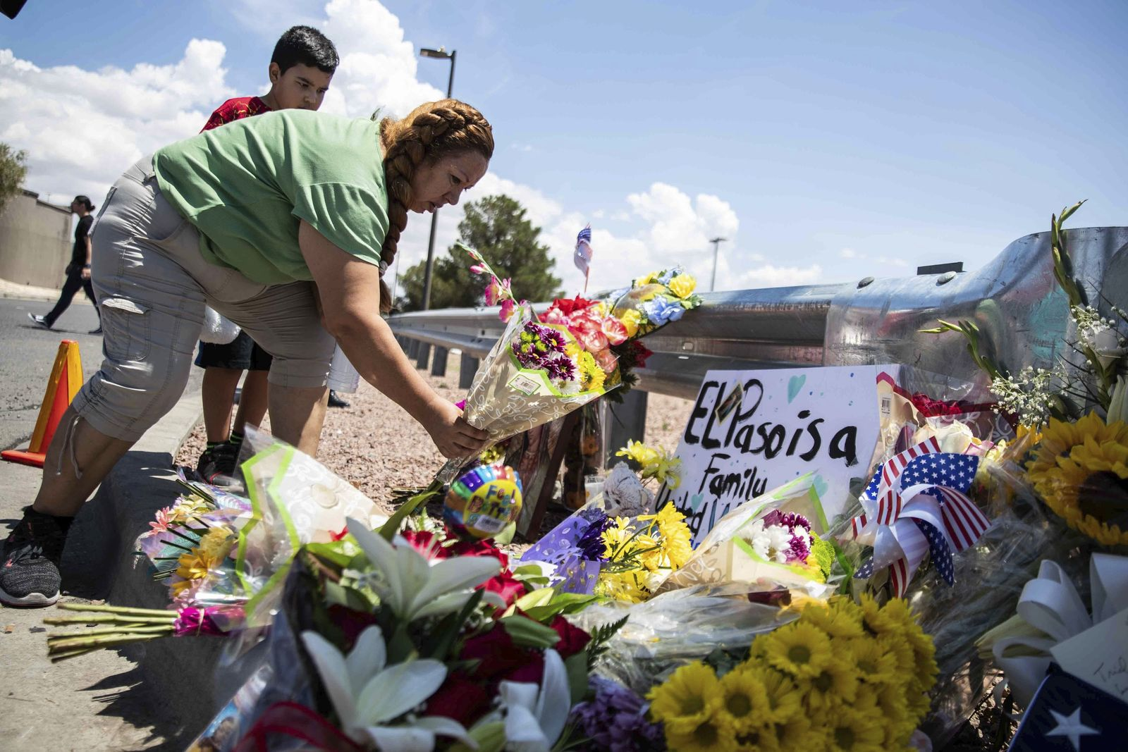 Carmen Roldan brings some flowers to honor the memory of the victims of the mass shooting occurred in Walmart on Saturday morning in El Paso on Sunday, August 4, 2019. (Lola Gomez/Austin American-Statesman via AP)