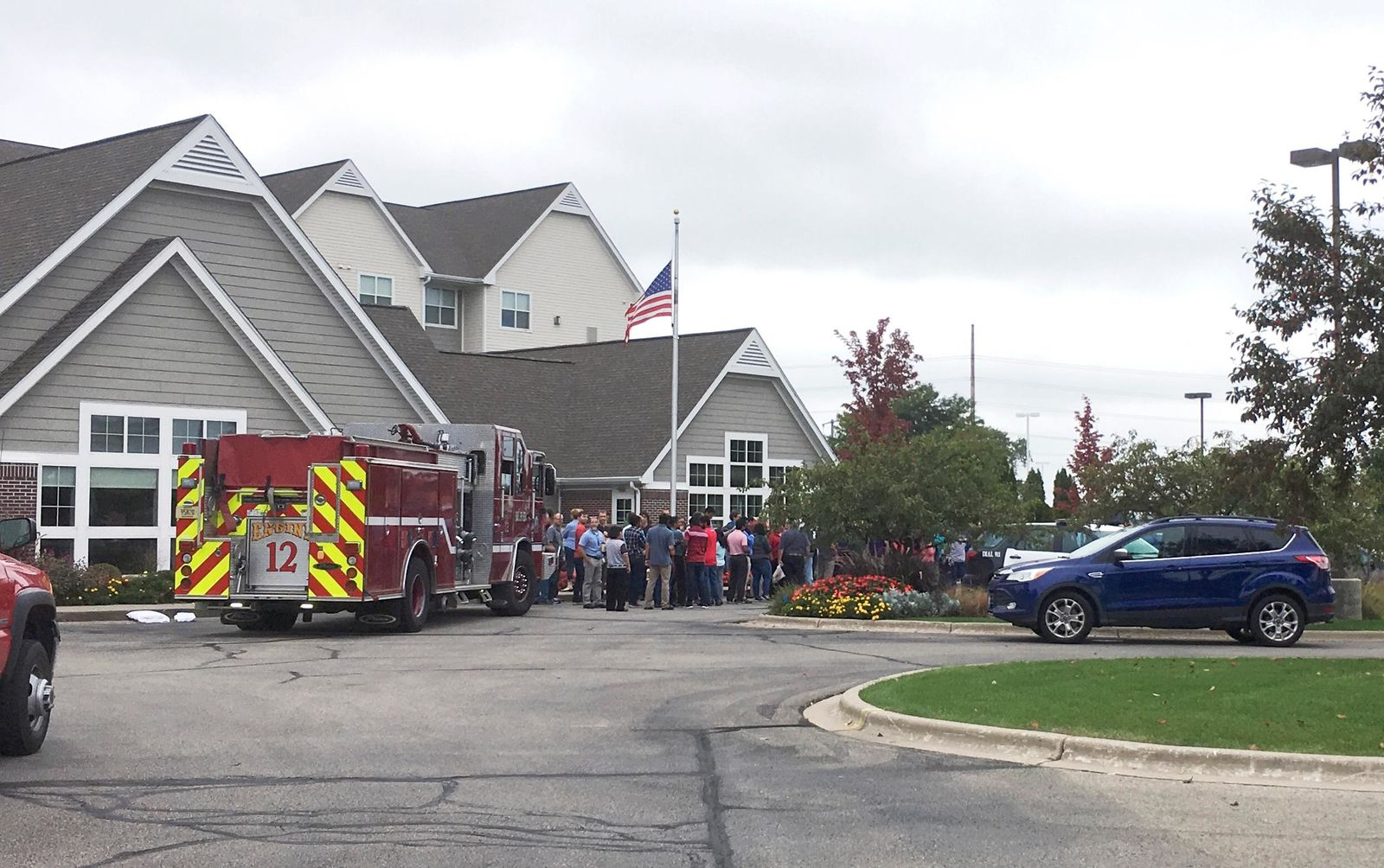 A fire truck and people evacuated are gathered at a hotel near the scene after a shooting was reported at a software company in Middleton, Wis., Wednesday, Sept. 19, 2018. (AP Photo/Todd Richmond)