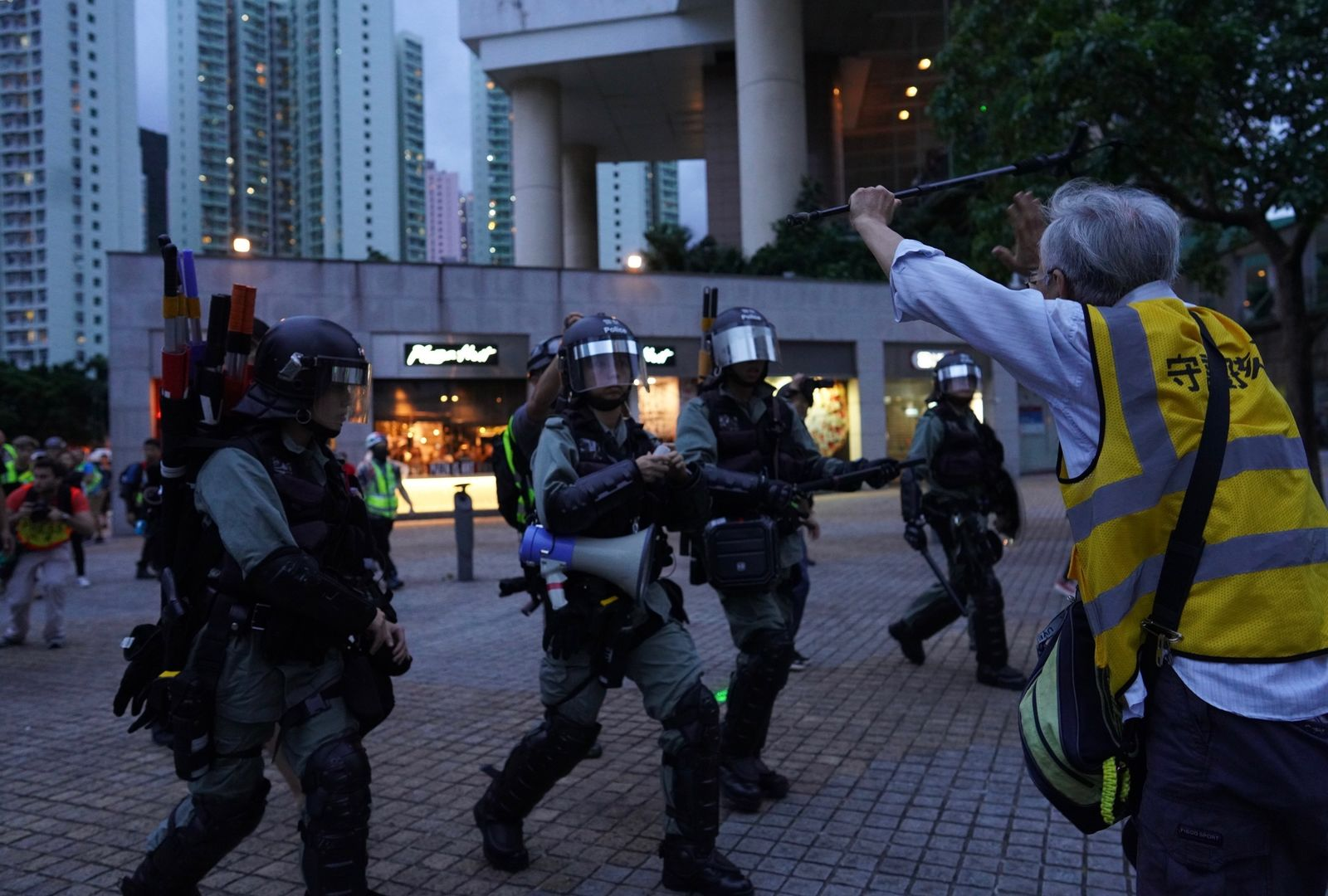 An elderly man tries to block policemen who arrive to arrest protesters at Tung Chung near airport in Hong Kong, Sunday, Sept.1, 2019.{ } (AP Photo/Vincent Yu)