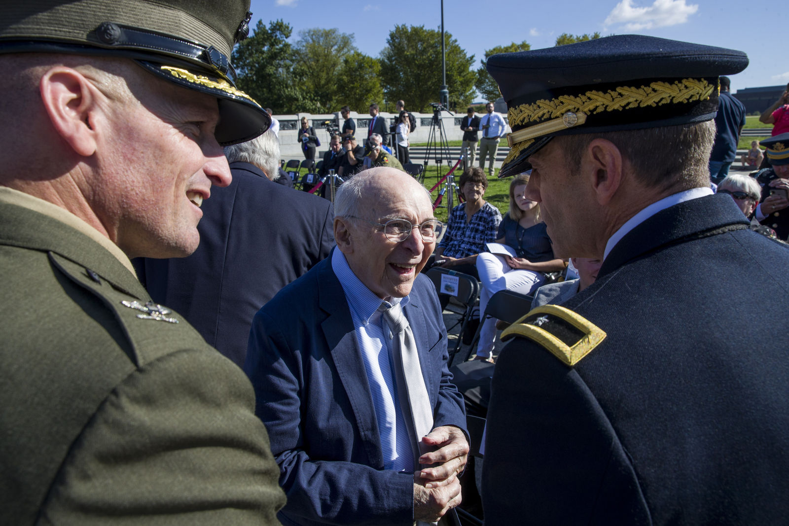 World War II veteran Buck Marsh, center, talks with two active duty military members before a ceremony to present a Bronze Star to Clarence Smoyer, at the World War II Memorial, Wednesday, Sept. 18, 2019, in Washington. (AP Photo/Alex Brandon)
