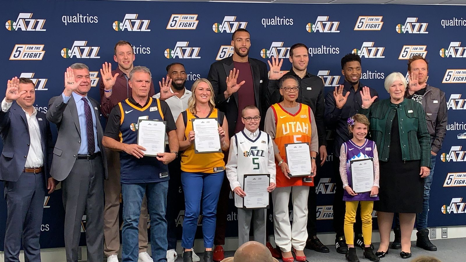 "Everyone poses for a photo op promoting ""5 For The Fight"" which aims to fund cancer research. (L-R) Steve Starks (CEO of Larry H. Miller Group of Companies), Jim Olson, president of the Utah Jazz, Joe Ingles (Jazz forward), Dave Warren (cancer fighter), Mike Conley (Jazz point guard), Dani Phillips (cancer fighter), Rudy Gobert (2-time Defensive Player of the Year, Utah Jazz Center, future All-Star) with Wyatt Page (young cancer fighter), Emma Houston (cancer fighter), Bojan Bogdanovic (Utah Jazz forward), Donovan ""Spida"" Mitchell (Utah Jazz guard, future MVP) with Baylee Semrow (young cancer fighter), Gail Miller (owner and chairperson of the Larry H. Miller Group of Companies), Ryan Smith (co-founder and CEO of Qualtrics and co-founder of Five For The Fight). (Photo: Adam Forgie, KUTV)"