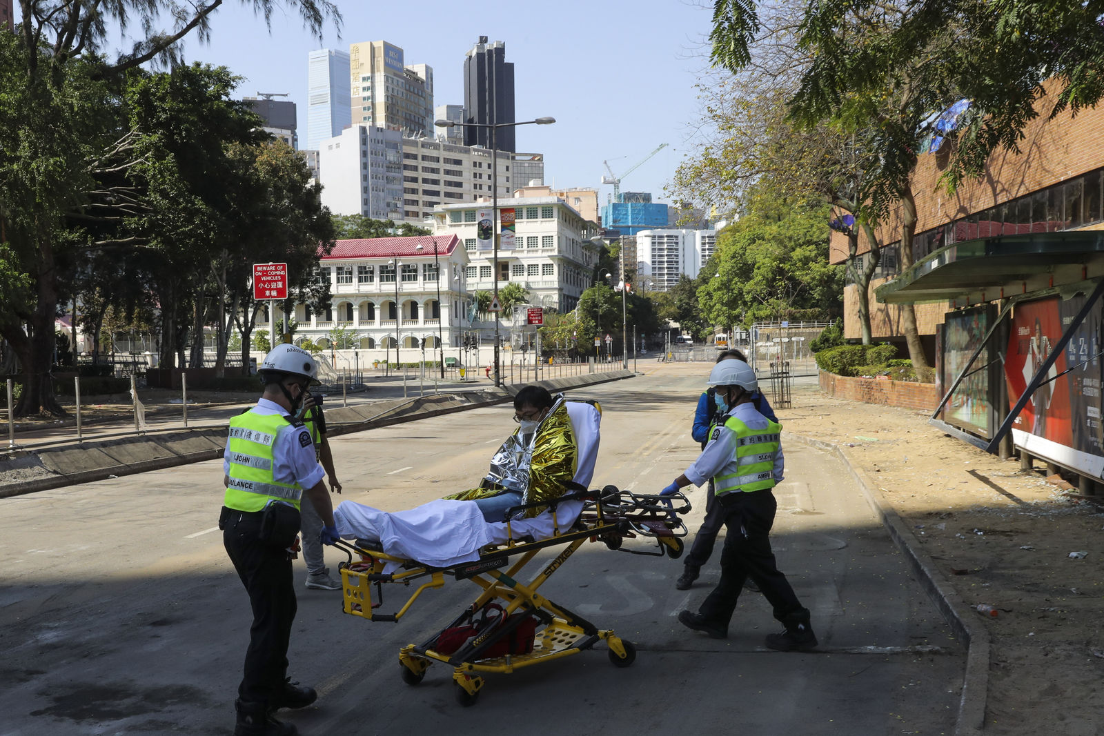 A protester is wheeled on a stretcher by first aid personnel as they leave the Polytechnic University campus in Hong Kong, Thursday, Nov. 21, 2019. (AP Photo/Vincent Thian)