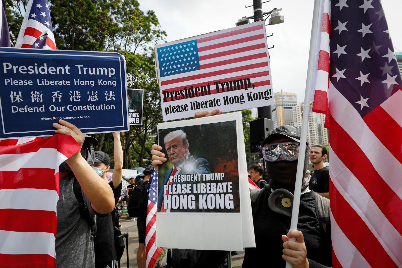 Protesters hold a placard featuring U.S. President Donald Trump and U.S. flags as they take part in a march at Victoria Park in Hong Kong, Sunday, July 21, 2019. Thousands of Hong Kong protesters marched from a public park to call for an independent investigation into police tactics.(AP Photo/Vincent Yu)