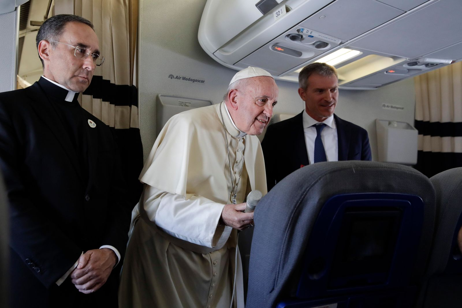 Pope Francis is flanked by his spokesperson Matteo Bruni, right, and Pope's trip organizer father Mauricio Rueda as he addresses journalists during his flight from Antamanarivo to Rome, Tuesday, Sept. 10, 2019, after his seven-day pastoral trip to Mozambique, Madagascar, and Mauritius. (AP Photo/Alessandra Tarantino)