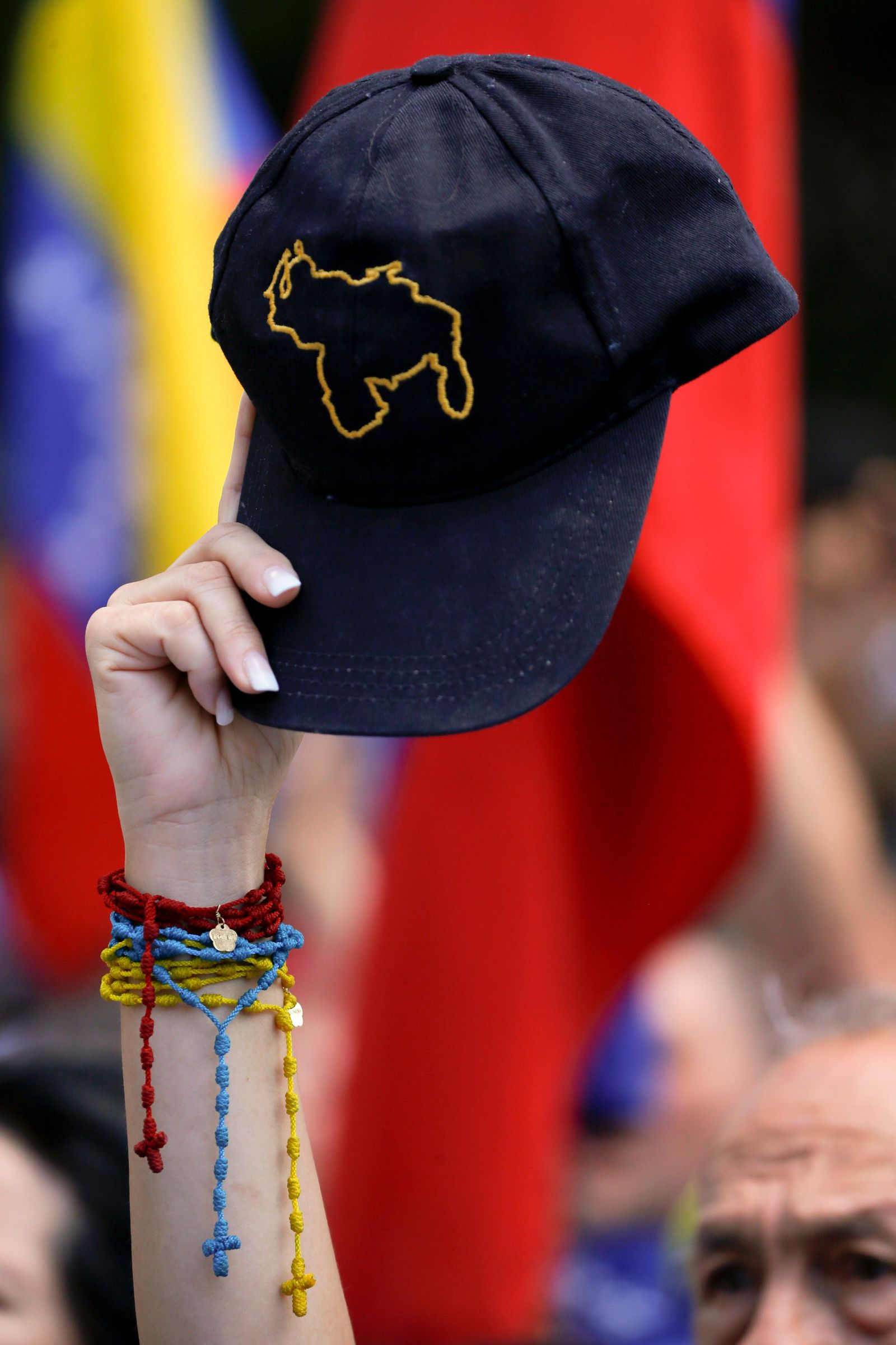 A supporter of opposition leader and self-proclaimed interim president Juan Guaido holds a cap with the outline of Venezuela's map during a rally to protest outages that left most of the country scrambling for days in the dark in Caracas, Venezuela, Saturday, April 6, 2019. (AP Photo/Fernando Llano)