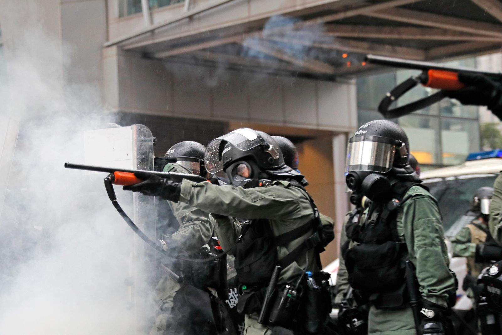 Riot policemen fire weapons during a confrontation with demonstrators during a protest in Hong Kong, Sunday, Aug. 25, 2019. (AP Photo/Kin Cheung)