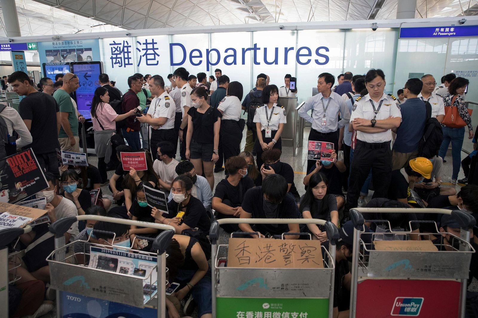 Airport security personnel stand guard as travelers walk past protesters holding a sit-in rally at the departure gate of the Hong Kong International Airport in Hong Kong, Tuesday, Aug. 13, 2019 (AP Photo/Vincent Thian)