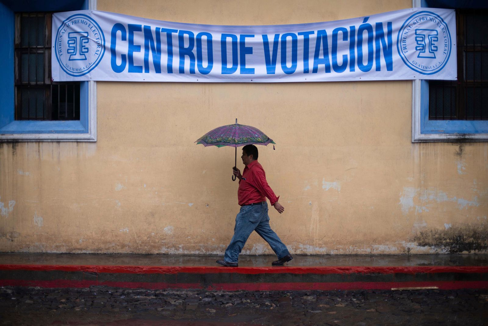 A man walks in the rain to a polling station during general elections in Antigua, Guatemala, Sunday, June 16, 2019.{ } (AP Photo/Santiago Billy)