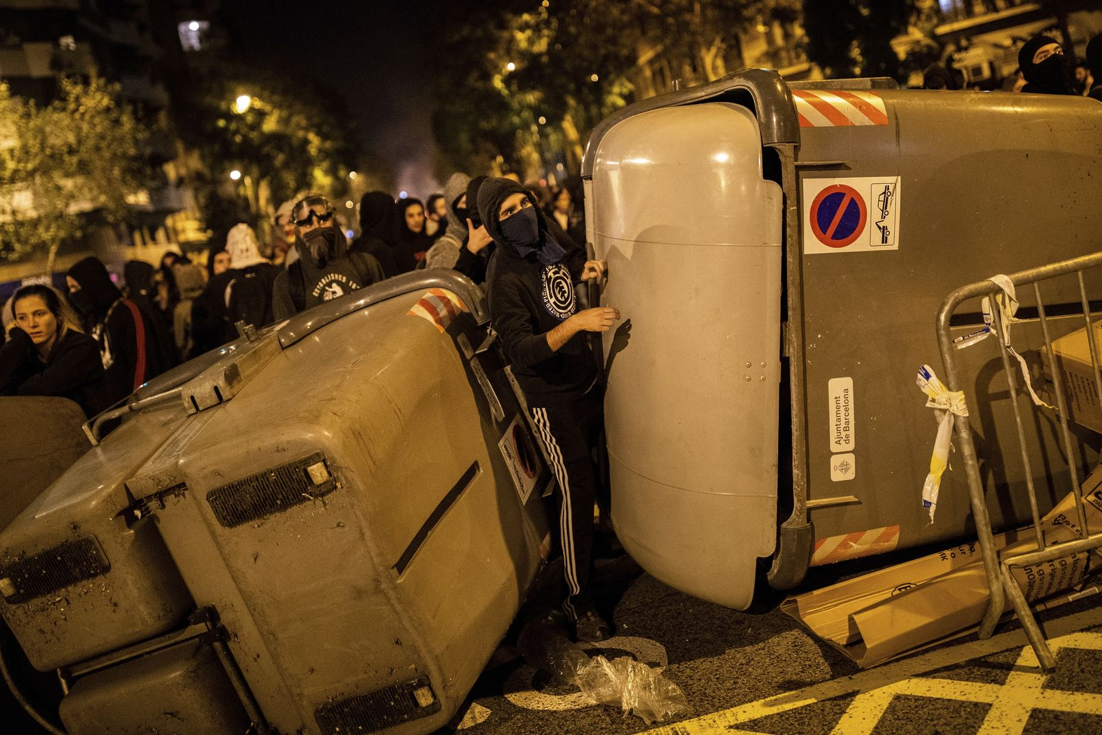 Demonstrators take shelter behind a barricade during clashes with police in Barcelona, Spain, Wednesday, Oct. 16, 2019. (AP Photo/Bernat Armangue)