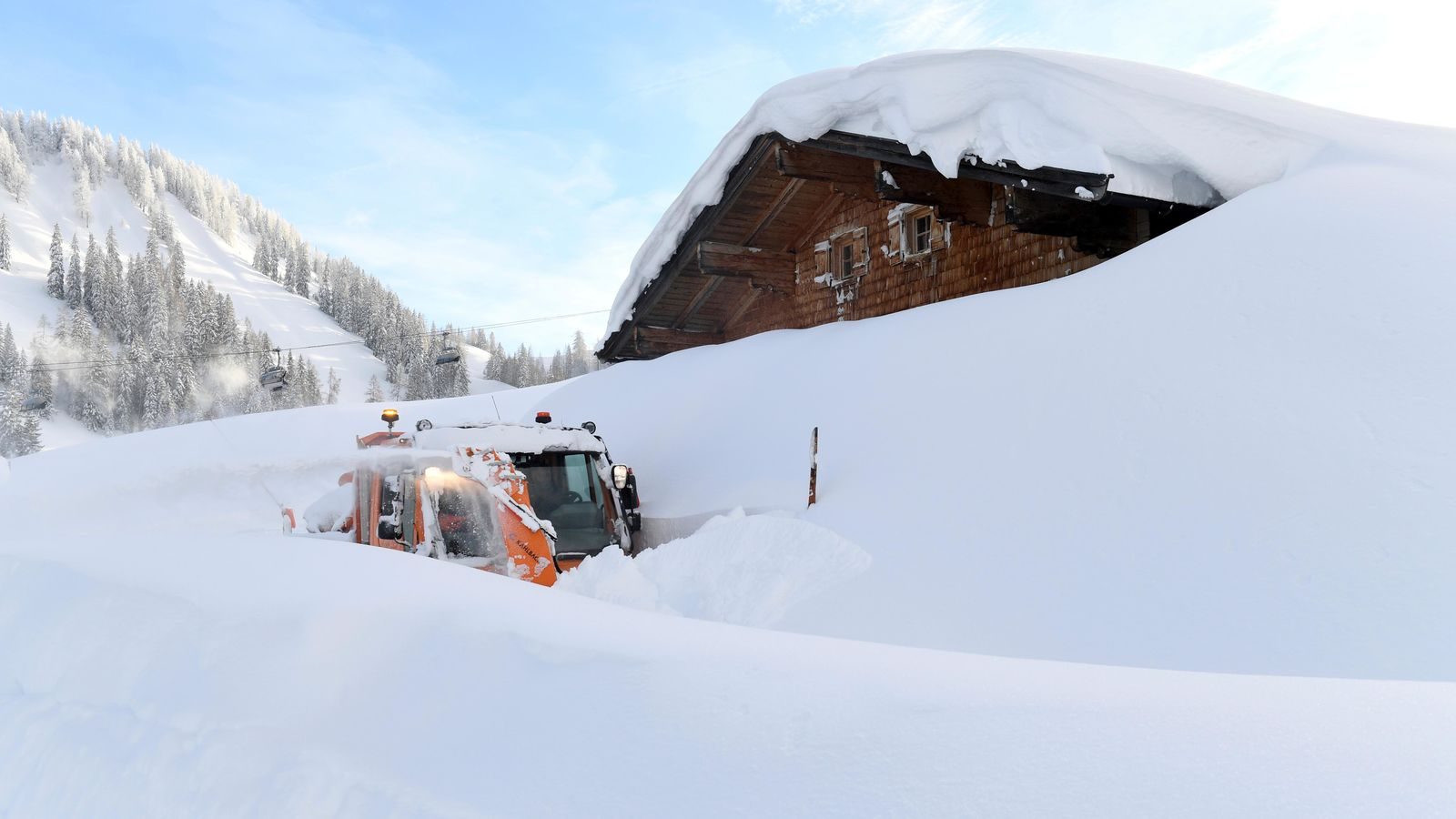A snow blower is seen on the Loferer Alp in Lofer, Austrian province of Salzburg, Friday, Jan. 11, 2019. In Salzburg, all parks, public gardens, play areas and cemeteries were closed on Friday because of the danger of trees falling under the weight of snow.(AP Photo/Kerstin Joensson)