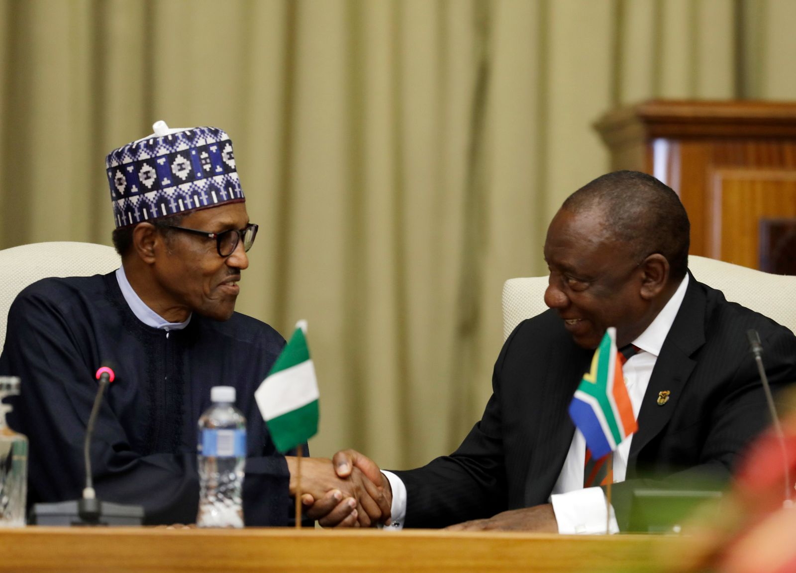 Nigerian President Muhammadu Buhari, left, and South Africa's President, Cyril Ramaphosa, shake hands as they meet after a welcoming ceremony in Pretoria, South Africa Thursday, Oct. 3, 2019.(AP Photo/Themba Hadebe)