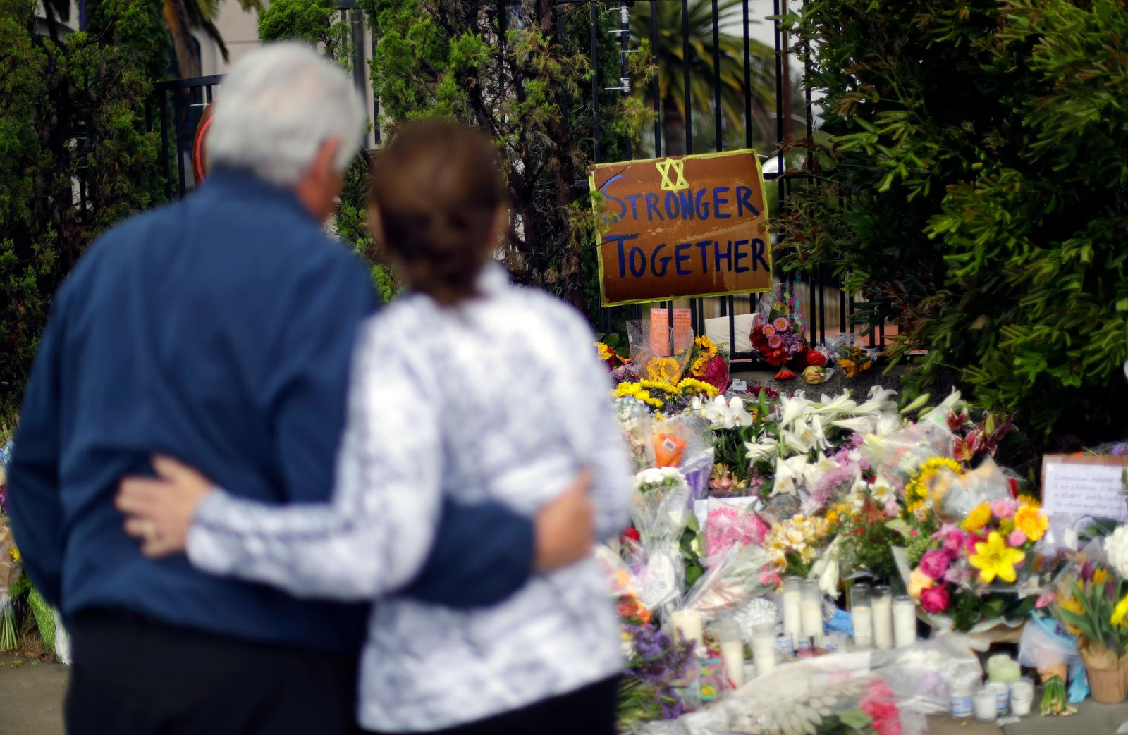 A couple embrace near a growing memorial across the street from the Chabad of Poway synagogue in Poway, Calif., on Monday,, April 29, 2019. (AP Photo/Greg Bull)