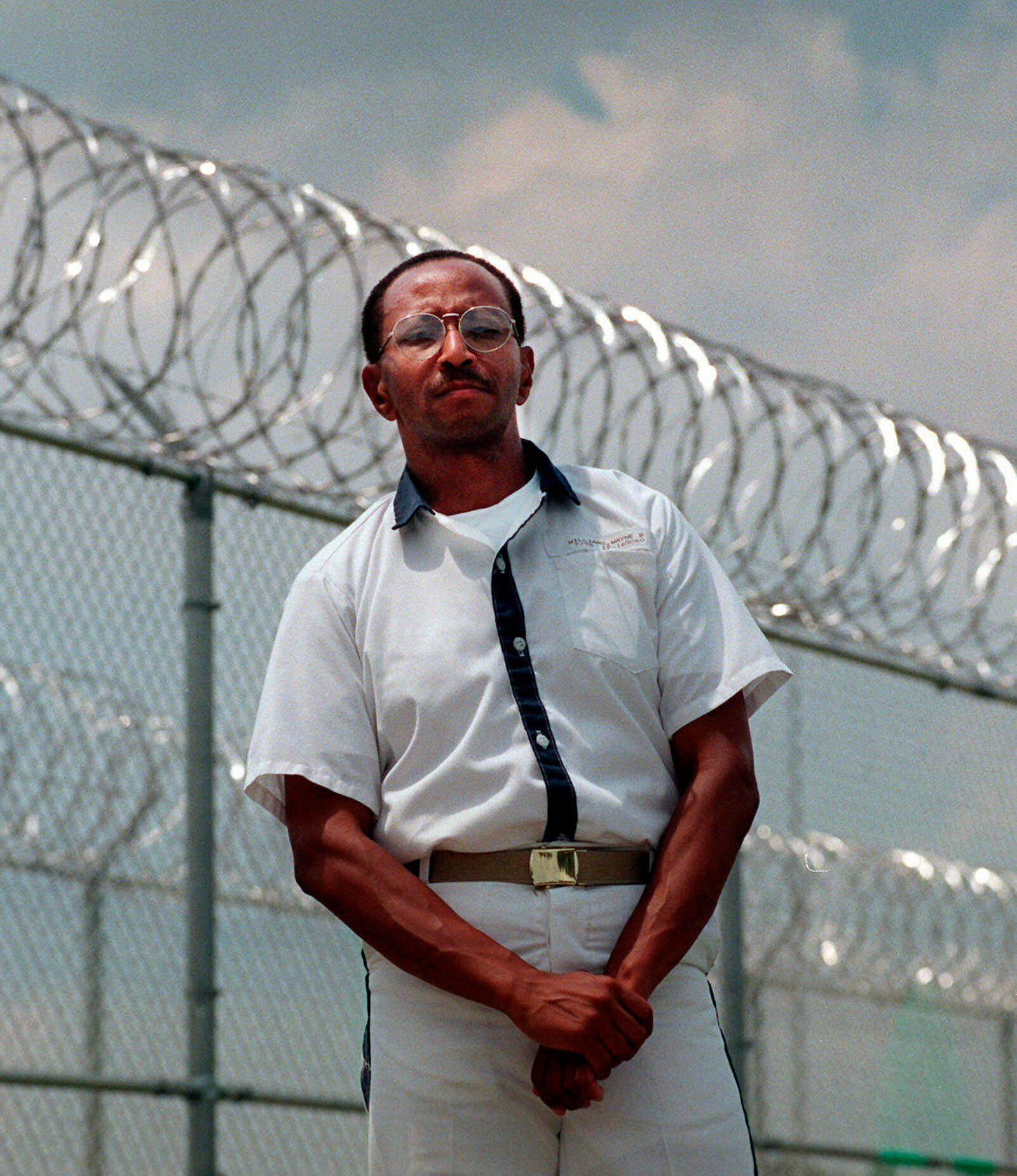 FILE - In this May 24, 1999 file photo, convicted killer Wayne Williams poses along the fence line at Valdosta Sate Prison, Valdosta, Ga. (AP Photo/John Bazemore, File)