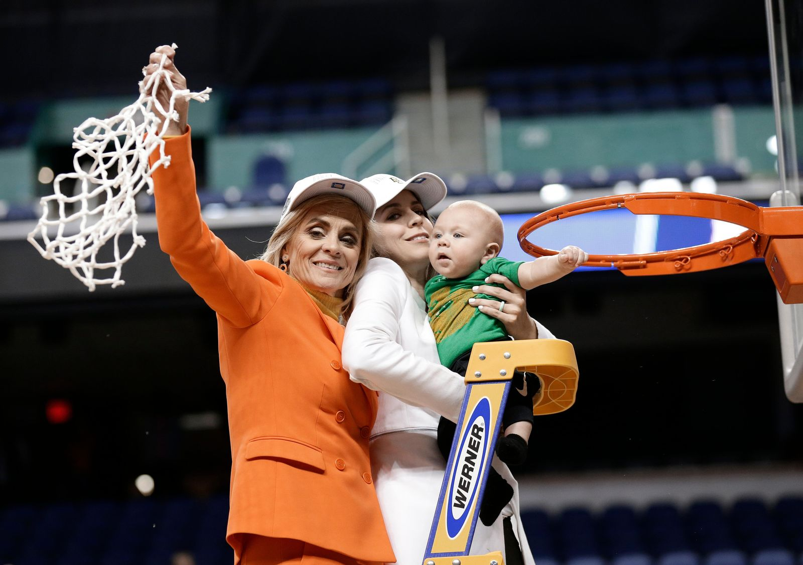 Baylor head coach Kim Mulkey, left, waves the net as she celebrates with her daughter Makenzie Fuller, center, and grandson Kannon Fuller, right, after Baylor defeated Iowa in a regional final women's college basketball game in the NCAA Tournament in Greensboro, N.C., Monday, April 1, 2019. (AP Photo/Gerry Broome)