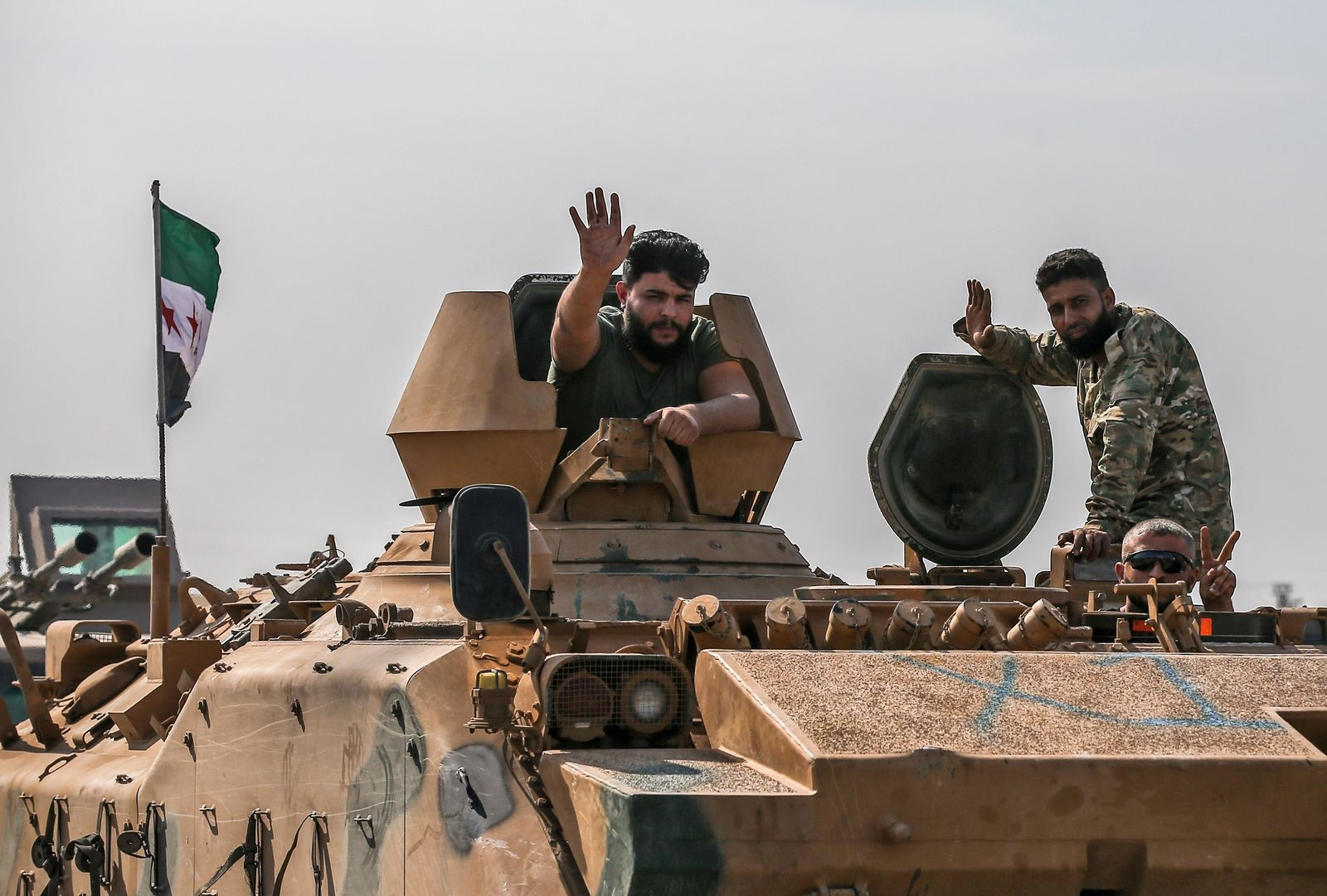 Turkish-backed Syrian opposition fighters on an armoured personnel carrier wave as they drive to cross the border into Syria, in Akcakale, Sanliurfa province, southeastern Turkey, Friday, Oct. 18, 2019. (AP Photo/Emrah Gurel)