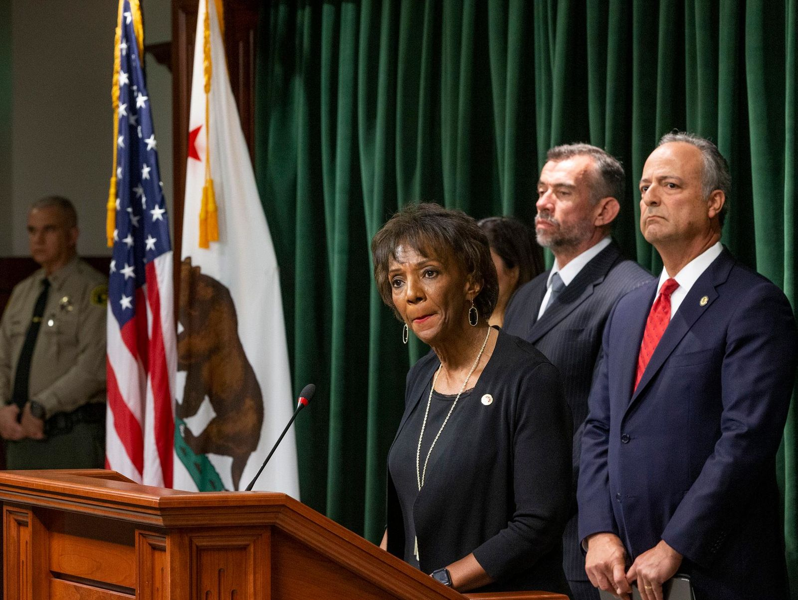 Los Angeles County District Attorney, Jackie Lacey, at podium, is joined by deputy special agent in charge of the DEA's Los Angeles division, William Bodner, second from right, and U.S. Attorney Nick Hanna, far right, during a news conference about the arrest of Ed Buck the prominent LGBTQ political activist, in Los Angeles, Thursday, Sept. 19, 2019. Federal prosecutors will ask a judge to hold Buck without bond pending his trial on charges connected to a drug death at his Los Angeles-area home. (AP Photo/Damian Dovarganes)