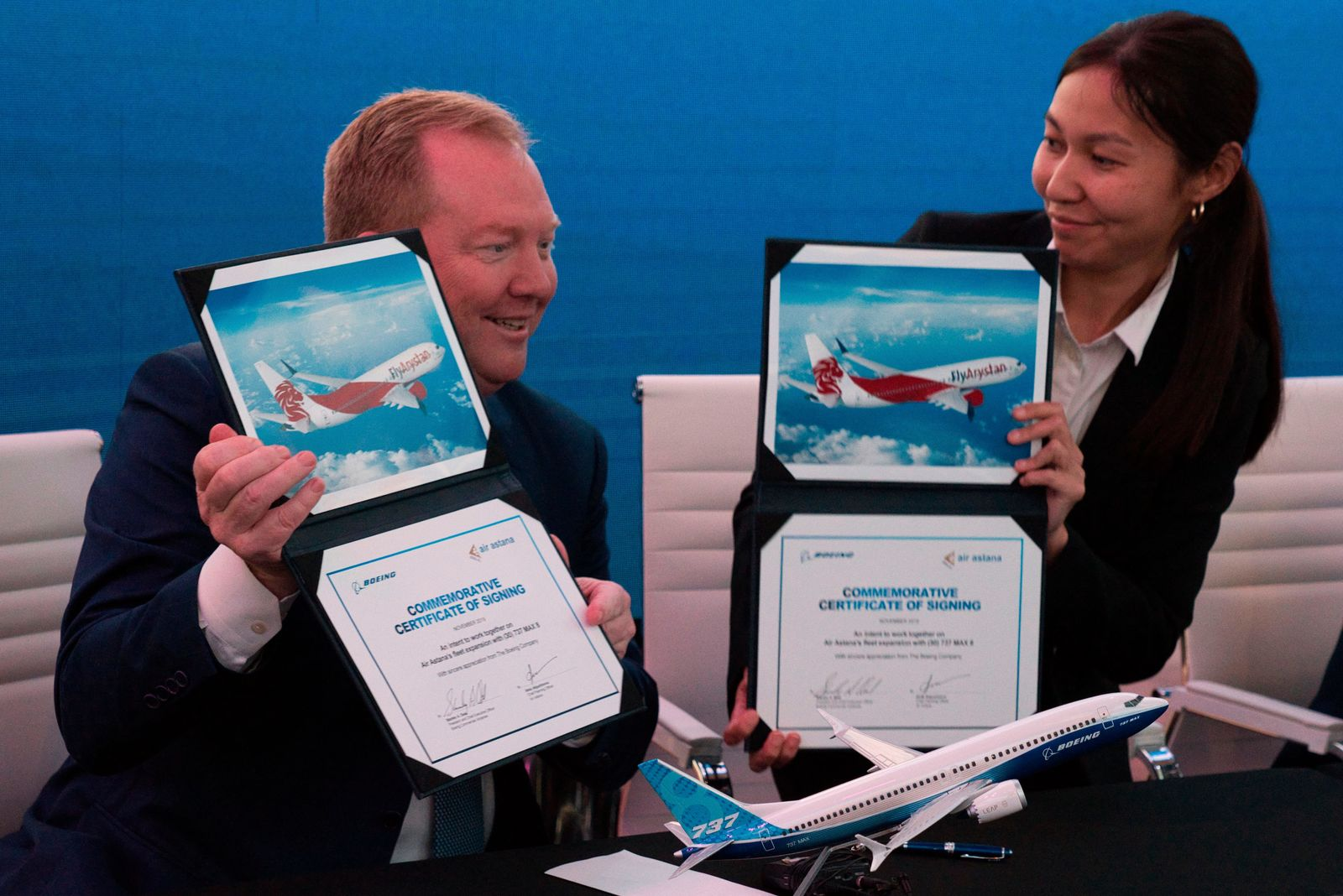 Boeing Commercial Airplanes president and CEO Stanley A. Deal, left, and Air Astana chief planning officer Alma Aliguzhinova pose at a news conference at the Dubai Airshow in Dubai, United Arab Emirates, Tuesday, Nov. 19, 2019. (AP Photo/Jon Gambrell)