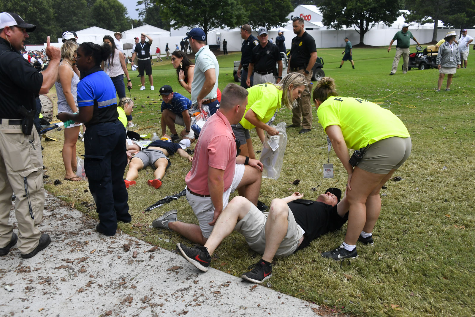 Spectators are tended to after a lightning strike on the course left several injured during a weather delay in the third round of the Tour Championship golf tournament Saturday, Aug. 24, 2019, in Atlanta. (AP Photo/John Amis)