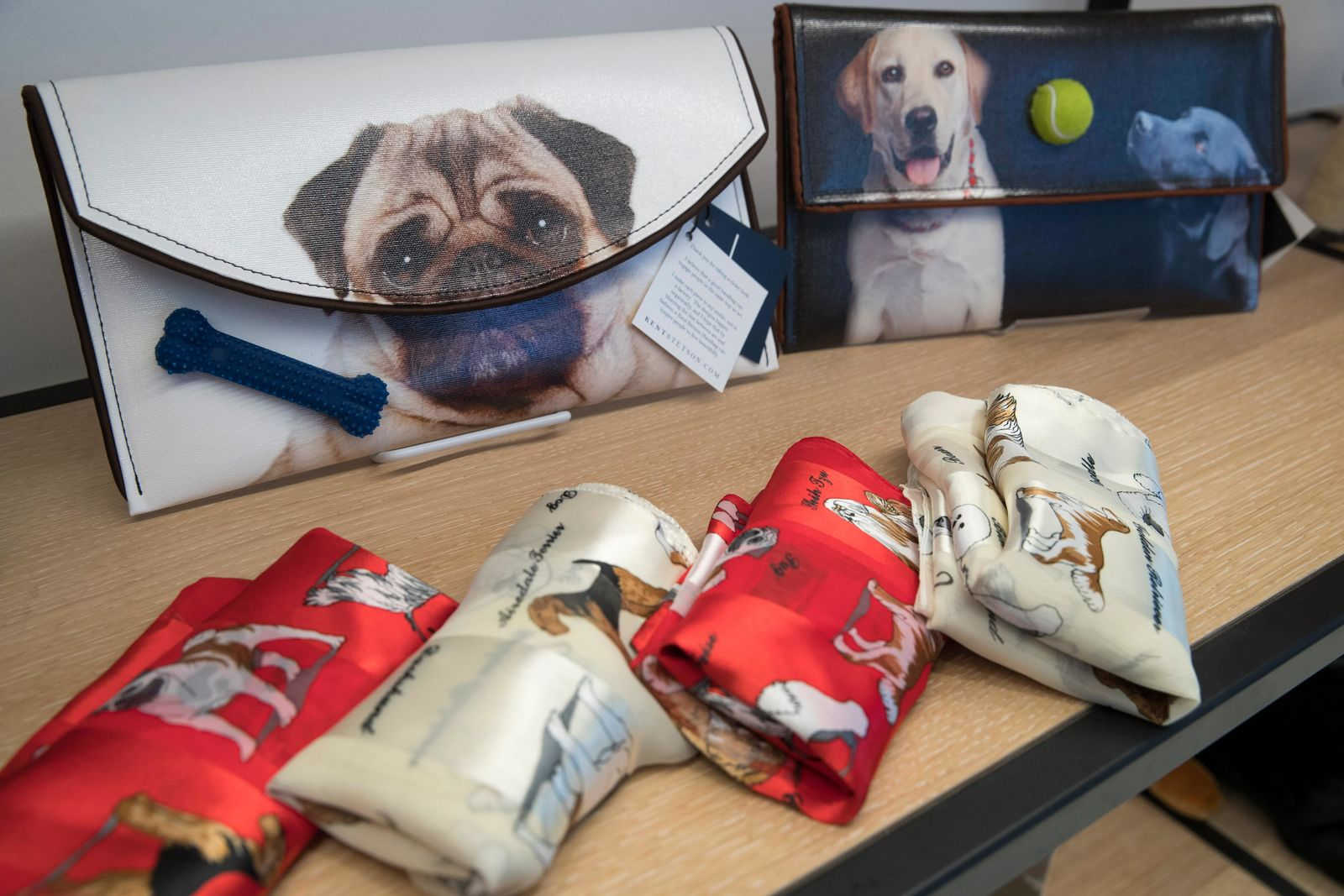 This Wednesday, Jan. 9, 2019, photo shows dog themed scarves and clutches that are on display for sale in the American Kennel Club Museum of the Dog's store in New York. The museum opens Feb. 8. (AP Photo/Mary Altaffer)